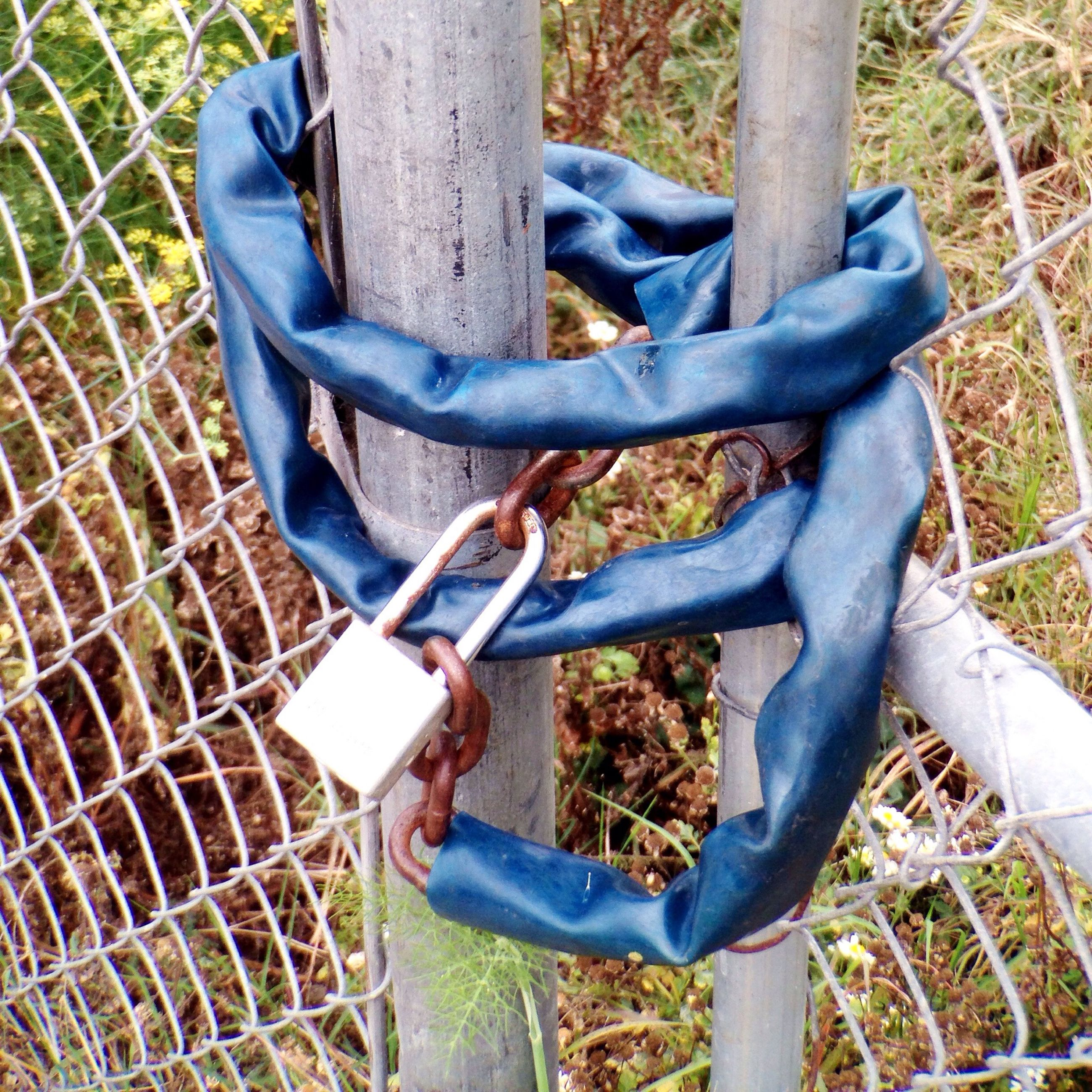 metal, fence, high angle view, field, low section, protection, grass, bicycle, childhood, chainlink fence, part of, chain, day, safety, outdoors, close-up, security, metallic