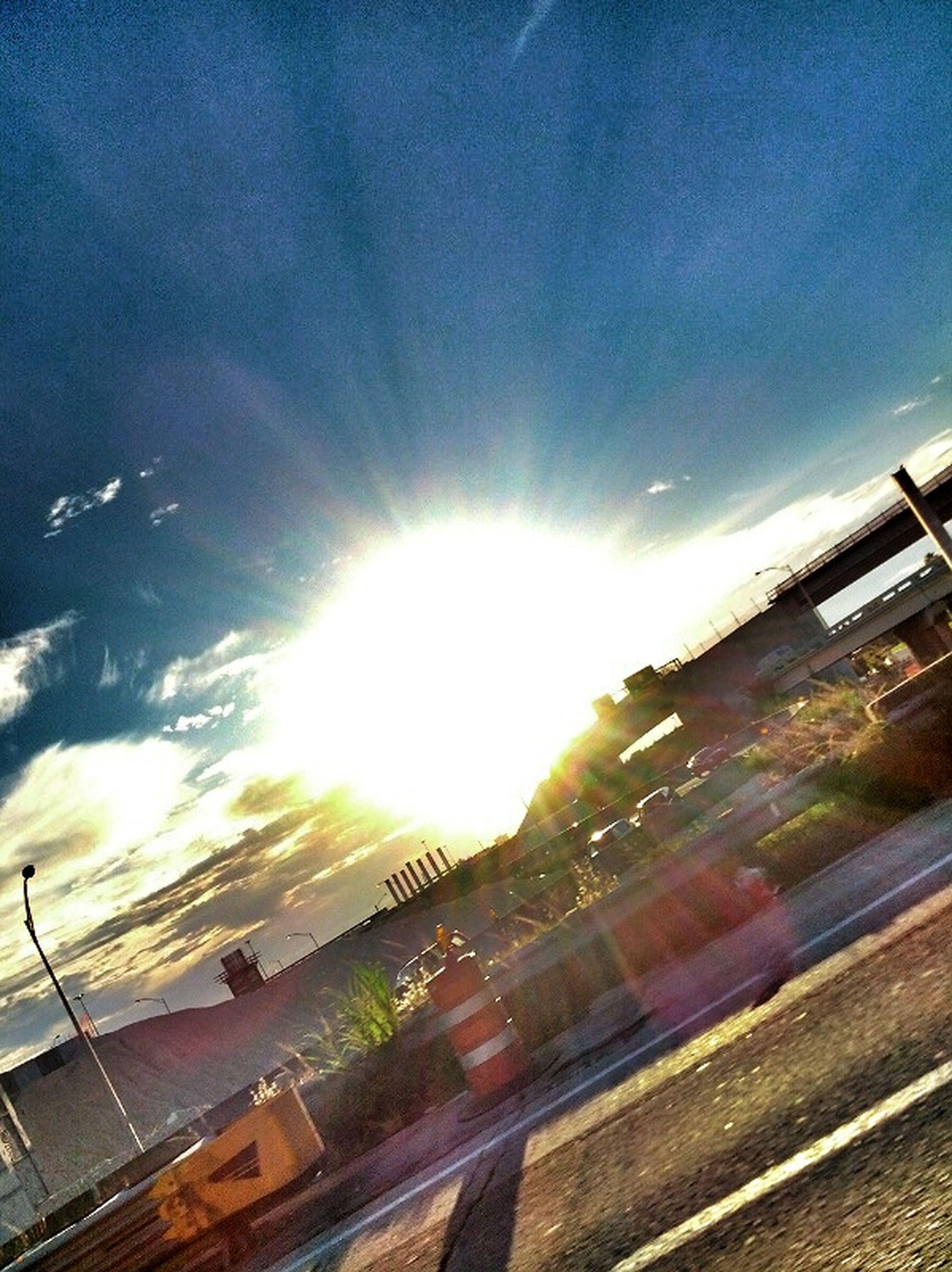 sunbeam, sun, sky, transportation, sunlight, lens flare, cloud - sky, road, built structure, architecture, building exterior, car, land vehicle, city, mode of transport, street, sunny, cloud, day, glass - material