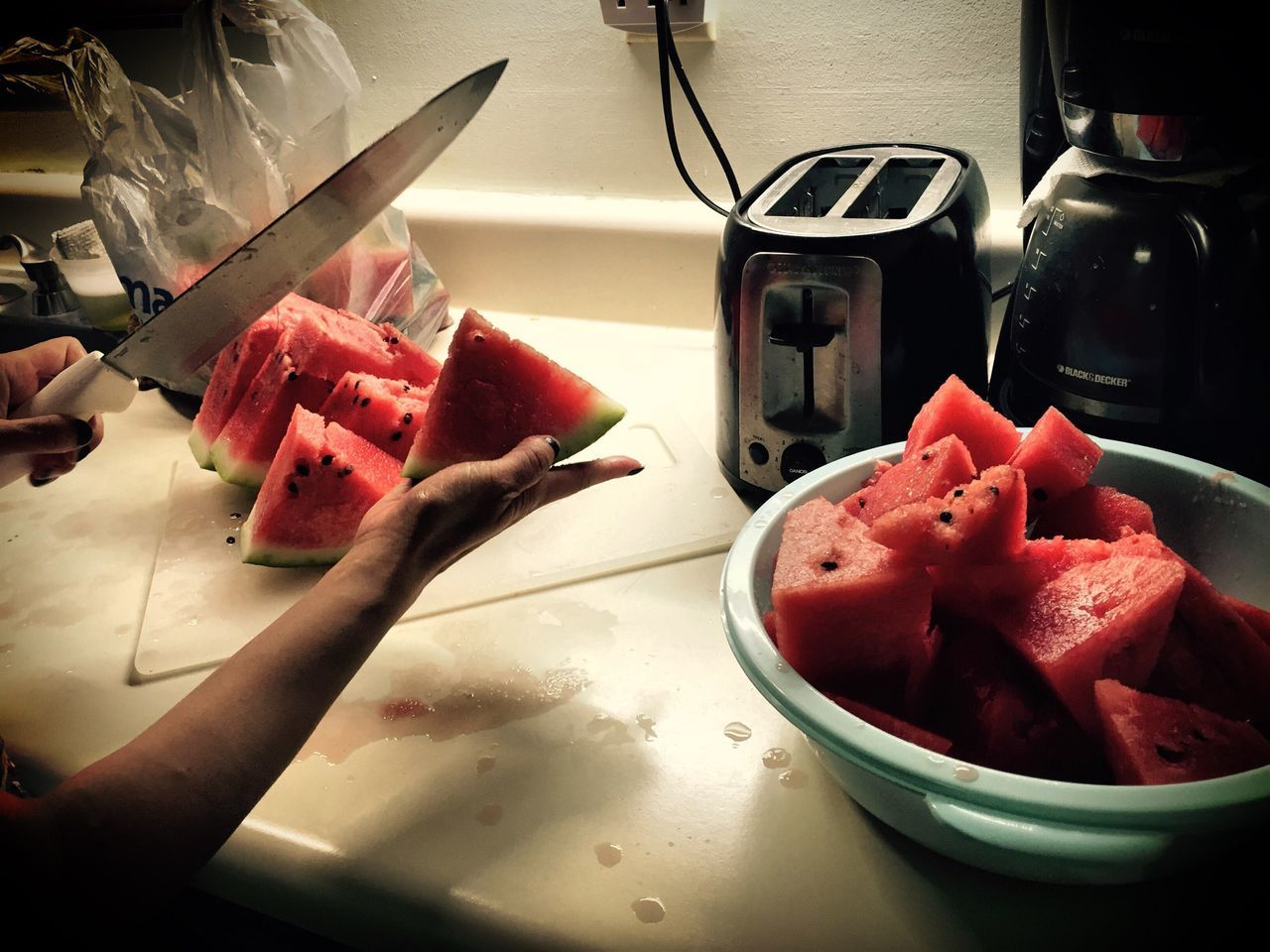 Cropped Hand Cutting Watermelon Slices At Kitchen Platform