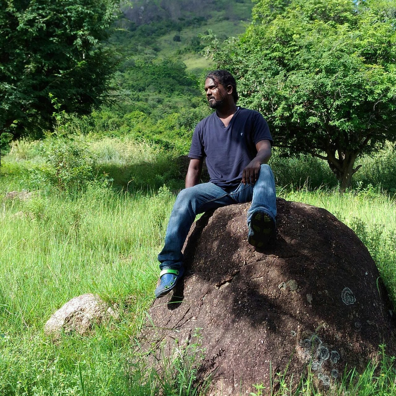 casual clothing, grass, sitting, real people, field, full length, mid adult men, jeans, tree, growth, day, nature, outdoors, relaxation, one person, young adult