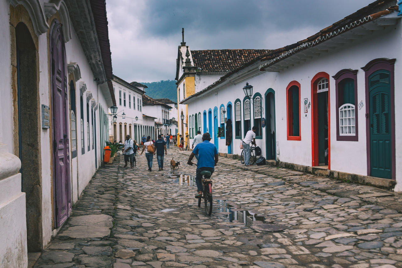 Cruising through the cobble stone streets in Parati. Architecture Bike Biking Building Exterior Built Structure Cobblestone Colonial Colorful Day Doors Large Group Of People Men Multi Colored Old Old Town Outdoors People Real People Sky Street The Street Photographer - 2017 EyeEm Awards The Way Forward Walking Windows Women Neighborhood Map