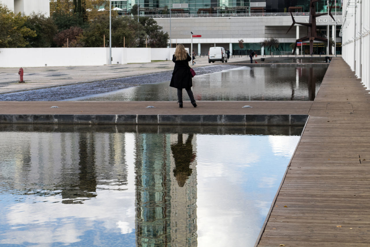 water, reflection, one person, full length, architecture, real people, puddle, outdoors, day, nature, sky, people