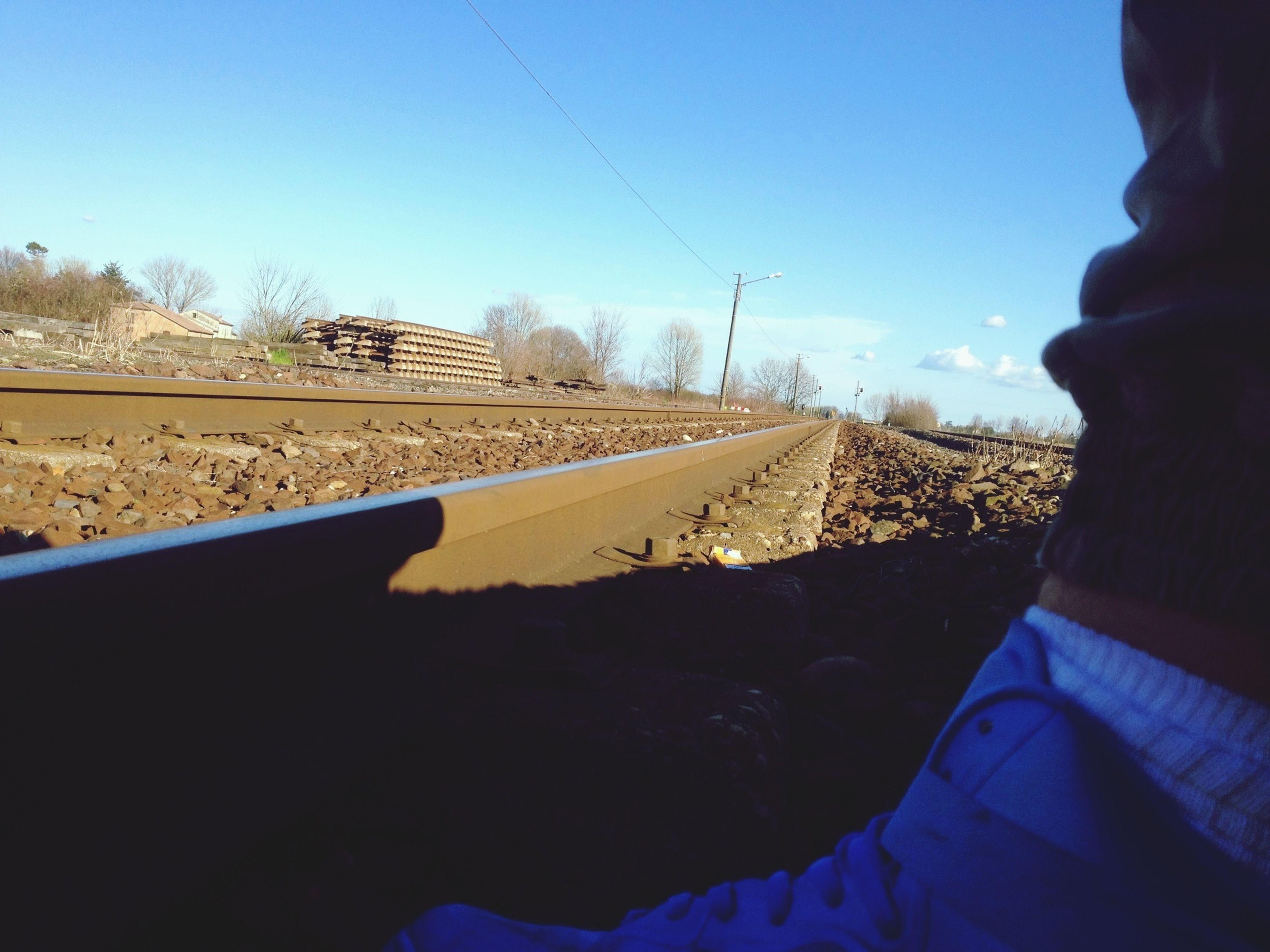 railroad track, transportation, clear sky, blue, sky, rail transportation, tree, diminishing perspective, the way forward, vanishing point, travel, day, public transportation, men, journey, railway track, copy space, outdoors