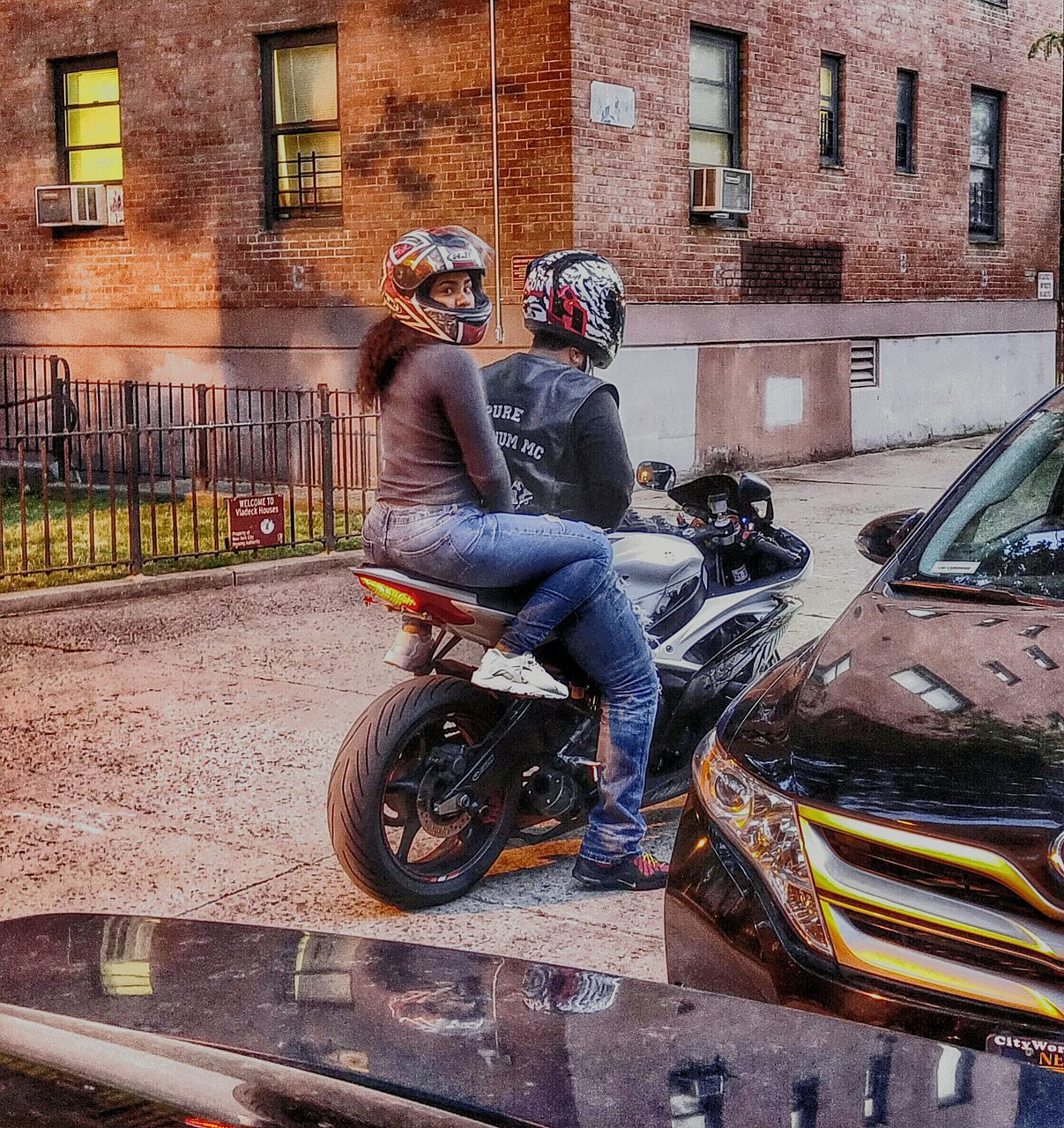 transportation, real people, two people, architecture, built structure, motorcycle, building exterior, land vehicle, mode of transport, lifestyles, full length, women, car, men, leisure activity, day, togetherness, outdoors, city, biker, headwear, young adult, adult, people, adults only