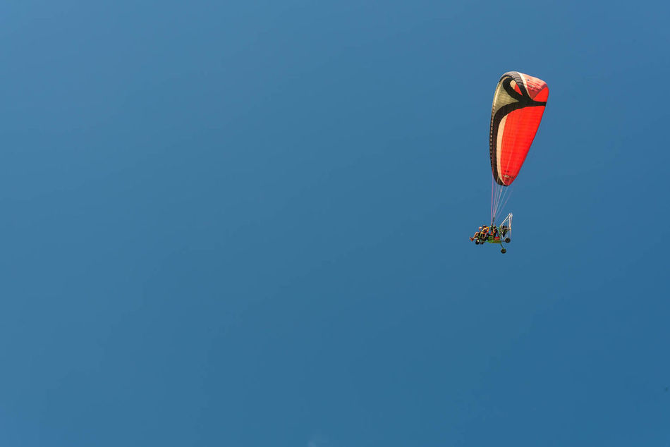 Enjoying flying action. Action Adventure Adventurous Blue Clear Sky Copy Space Day Enjoyment Extreme Sports Fly Flying Hot Air Balloon Low Angle View Nature One Person Outdoors Parachute Paragliding Science Sky Sport Technology Transportation