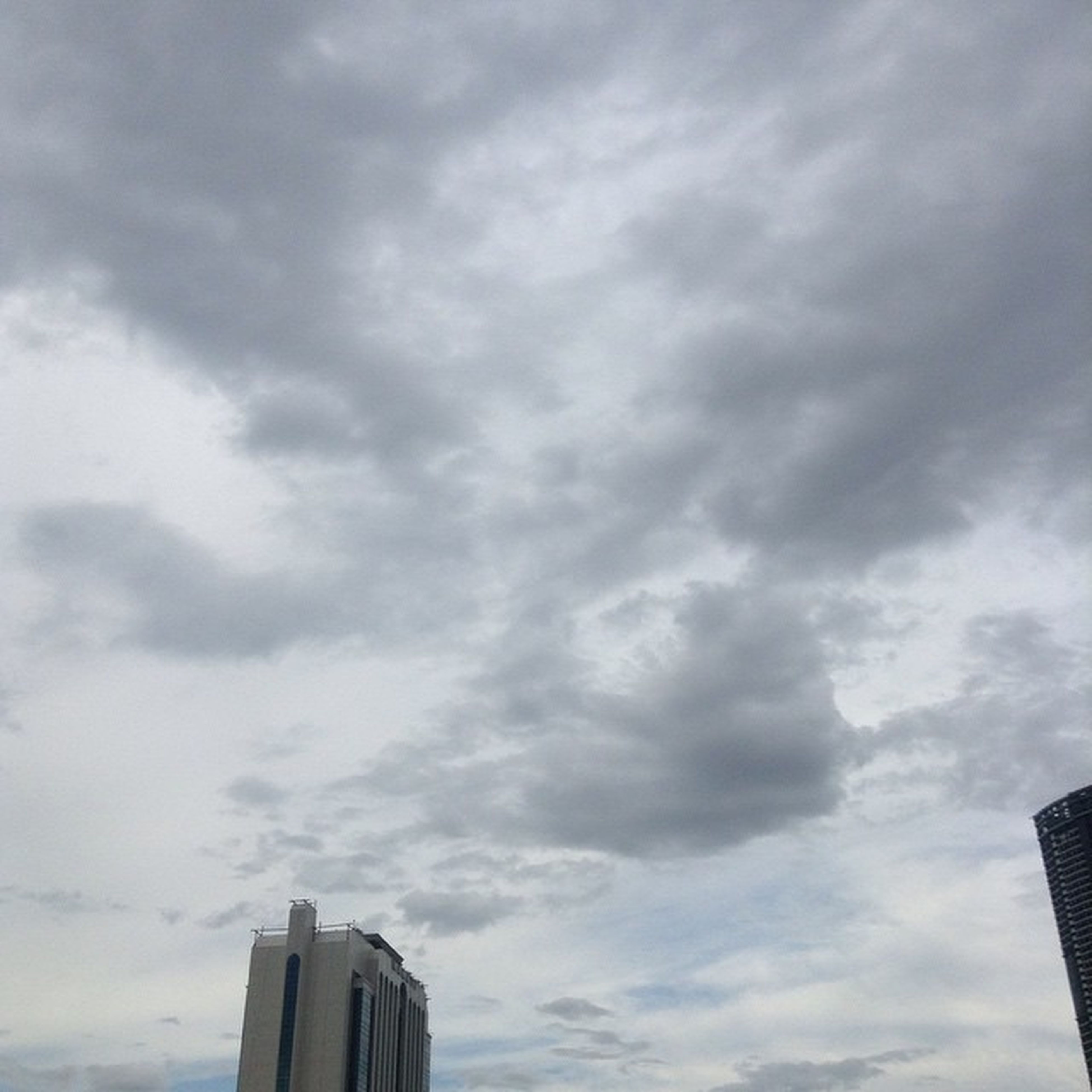 sky, low angle view, building exterior, architecture, cloud - sky, built structure, cloudy, cloud, weather, high section, building, overcast, outdoors, day, no people, cloudscape, city, tower, nature, storm cloud