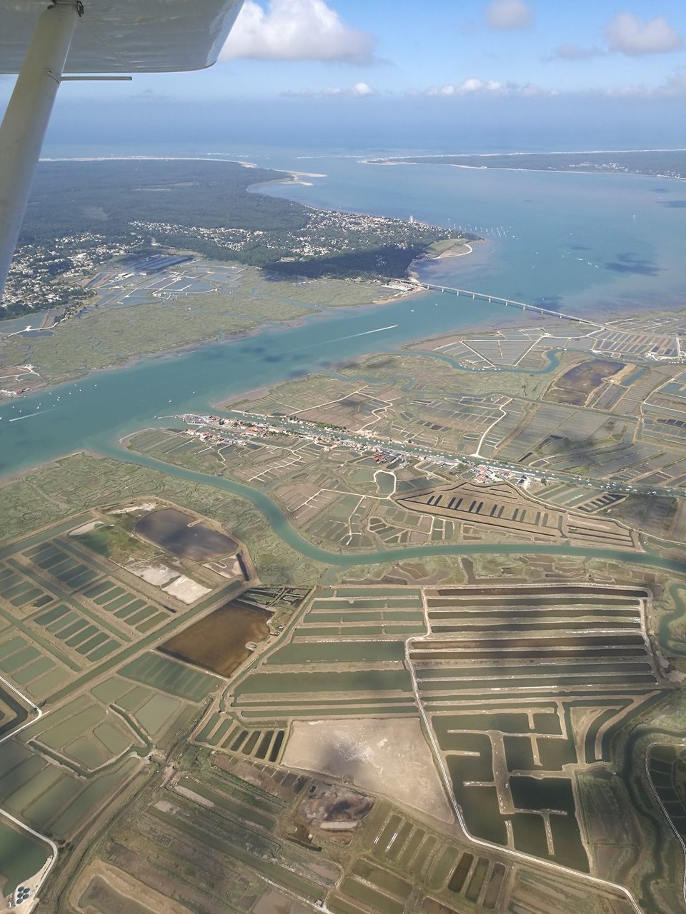 scenics, landscape, beauty in nature, aerial view, nature, tranquil scene, agriculture, tranquility, day, sea, sky, no people, field, outdoors, patchwork landscape, high angle view, rural scene, water, cloud - sky, horizon over water, airplane