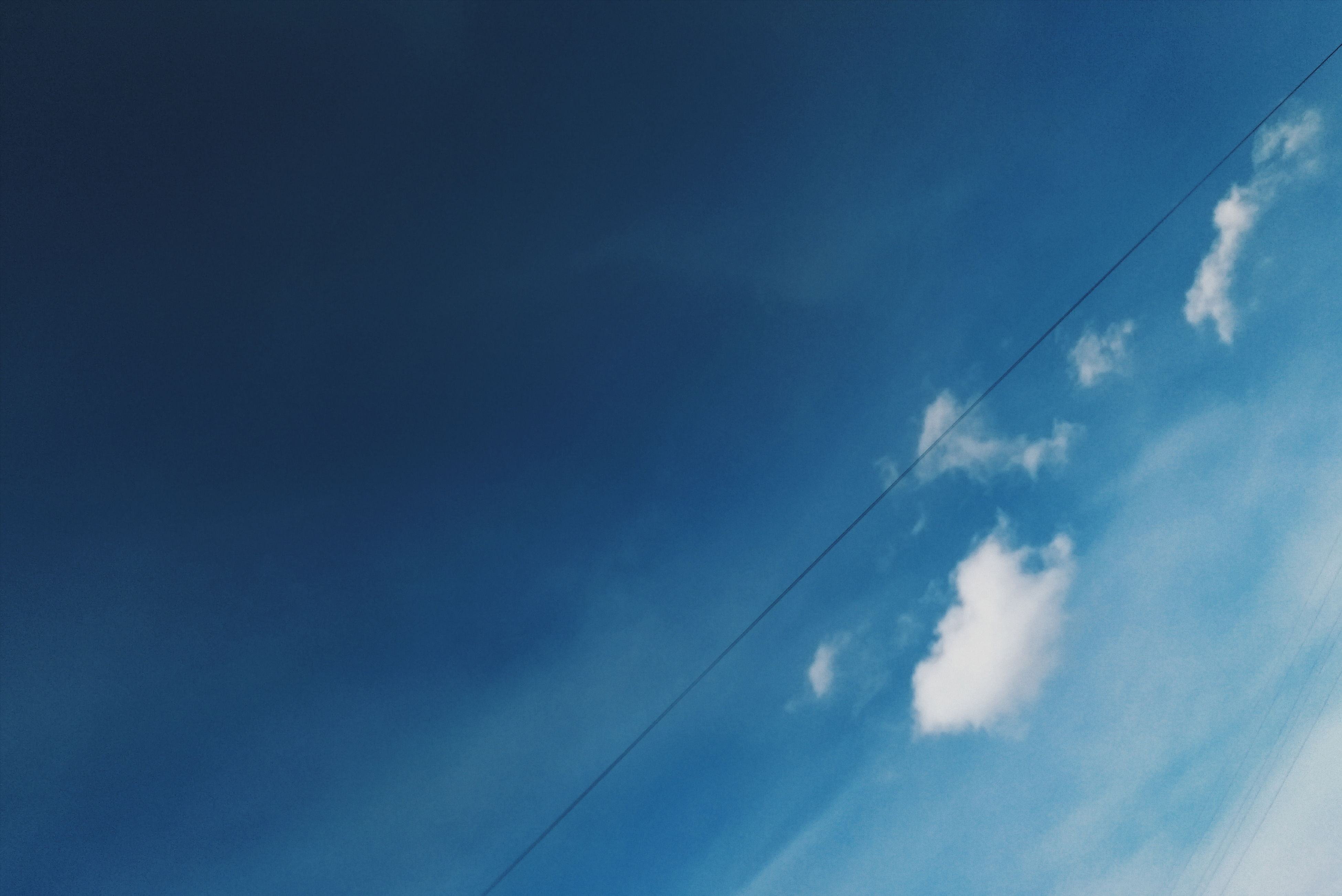 low angle view, blue, sky, power line, cable, cloud - sky, electricity, vapor trail, power supply, nature, cloud, connection, beauty in nature, tranquility, outdoors, no people, day, electricity pylon, scenics, copy space