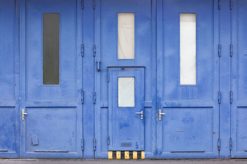 Huge, blue steel doors from a business in a commercial park with yellow and black stripes to mark the step Aging Process Architectural Feature Architecture Black Blue Building Exterior City Close-up Closed Door Entrance Front Door Full Frame Industry Metal Pattern Protection Rusty Steel Steps Striped Wall - Building Feature Weathered Window Yellow