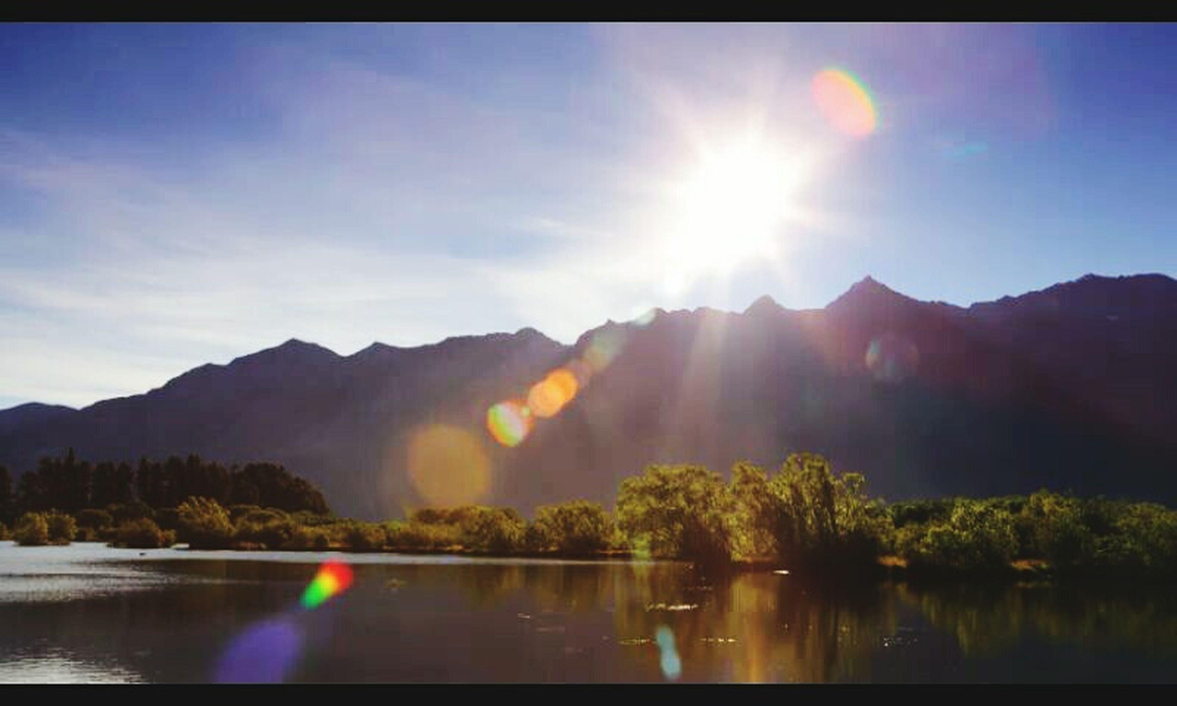 water, mountain, sun, scenics, sunbeam, tranquil scene, beauty in nature, mountain range, tranquility, lake, sky, sunlight, reflection, nature, lens flare, idyllic, river, waterfront, panoramic, cloud - sky