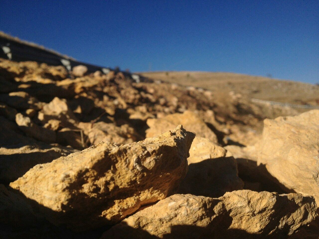 rock - object, sunlight, day, outdoors, no people, geology, clear sky, nature, tranquility, arid climate, blue, physical geography, landscape, shadow, sky, desert, close-up, beauty in nature