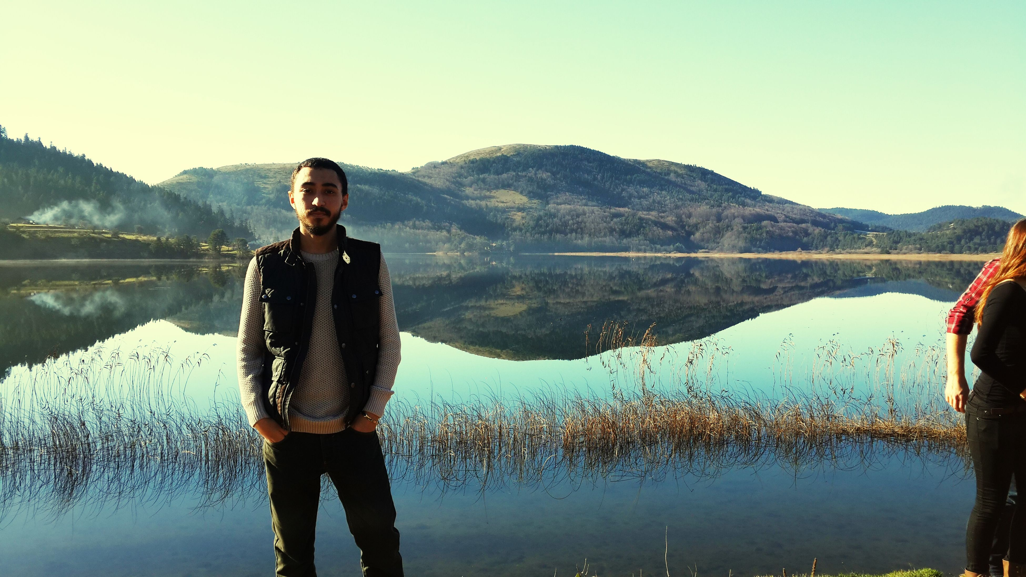 water, mountain, standing, lake, lifestyles, tranquility, leisure activity, tranquil scene, scenics, reflection, young adult, mountain range, three quarter length, clear sky, beauty in nature, casual clothing, nature, young men