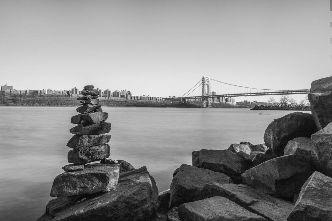 Pile of rocks stacked along the New Jersey Waterfront and the George Washington Bridge in the background. Architecture Black And White Bridge - Man Made Structure Built Structure City Clear Sky Connection Long Exposure No People Outdoors Pile Of Rocks River Rocks Rocks And Water Sky Stack Of Rocks Stacked Stacked Stones Water Waterfront