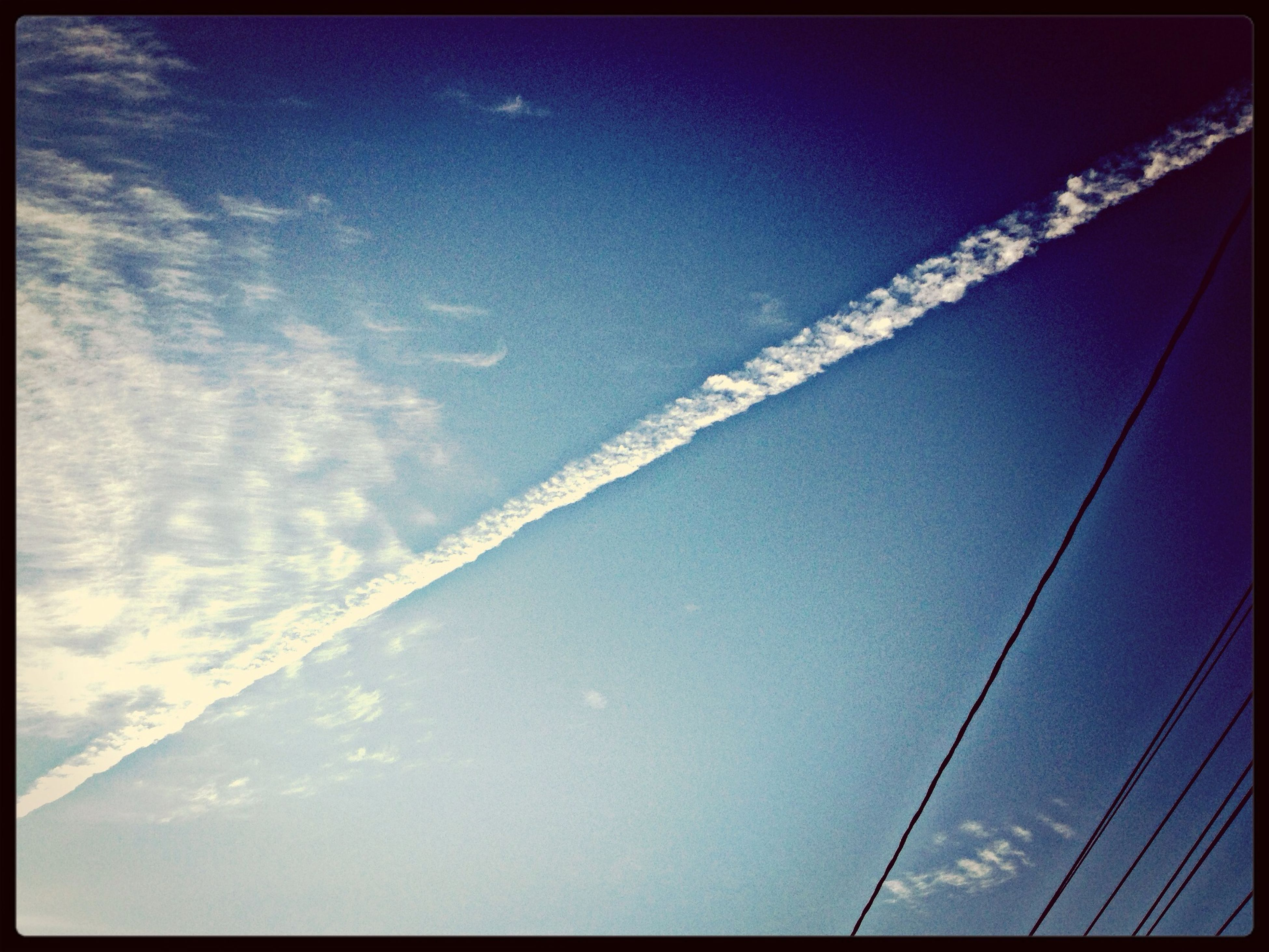 low angle view, transfer print, sky, connection, blue, auto post production filter, power line, nature, outdoors, cable, cloud - sky, beauty in nature, no people, day, electricity, vapor trail, clear sky, scenics, bridge - man made structure, transportation