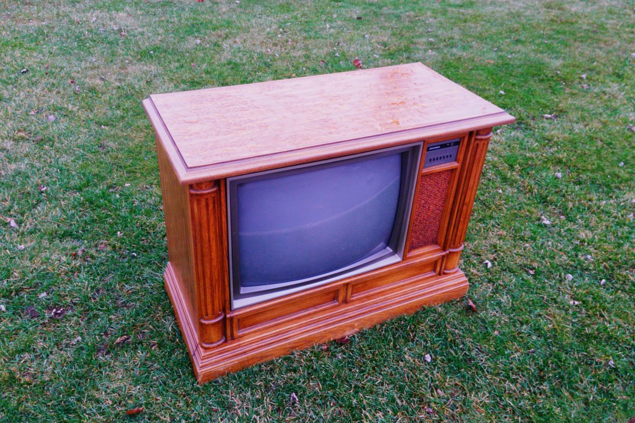 High Angle View Of Old Television Set On Grassy Field