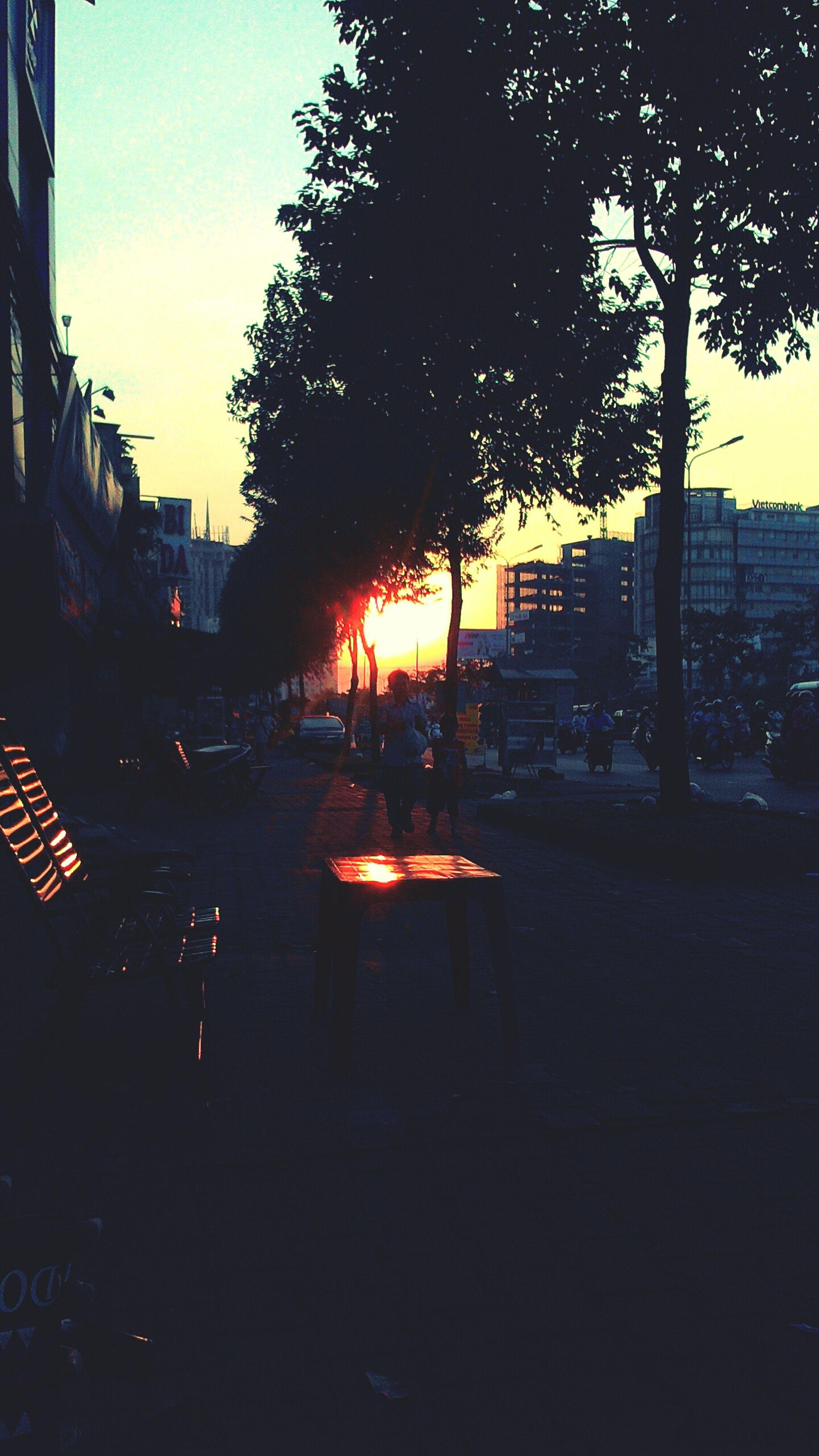 sunset, building exterior, city, architecture, built structure, car, transportation, street, land vehicle, silhouette, street light, mode of transport, tree, sky, road, city life, city street, sunlight, orange color, sun