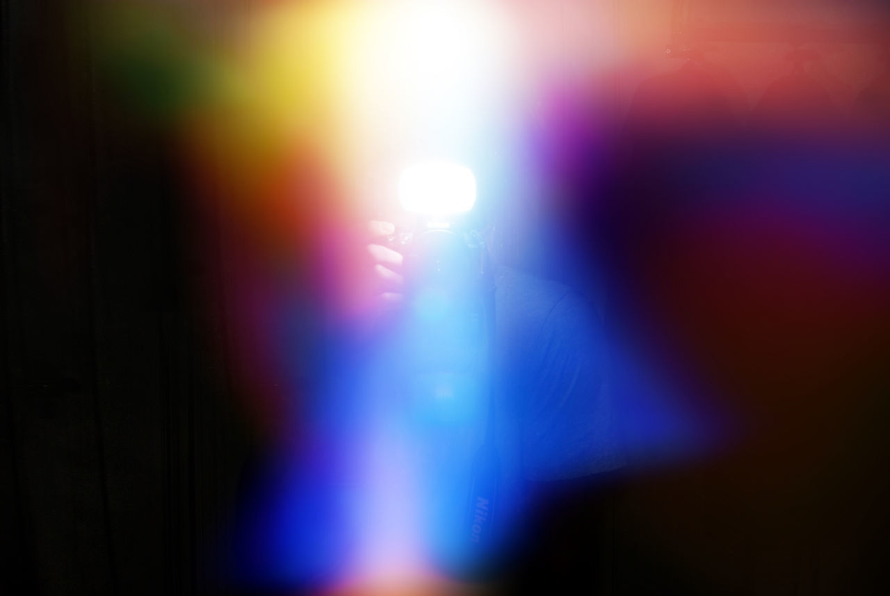 Defocused Image Of Person Photographing Amidst Colorful Lights
