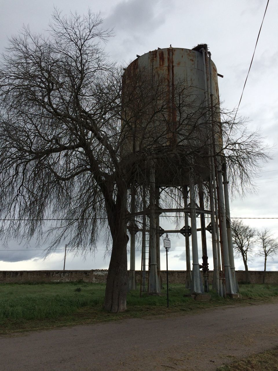 Bare Tree And Storage Tank On Field Against Sky