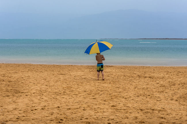 under my umbrella in DeadSea Beach Beauty In Nature Blue Casual Clothing Color Palette Colour Of Life Deadsea EyeEm Team Full Length Horizon Over Water Idyllic Leisure Activity Lifestyles Nature Outdoors Remote Scenics Sea Shore Tranquil Scene Tranquility Umbrella Vacations Pivotal Ideas Colors And Patterns
