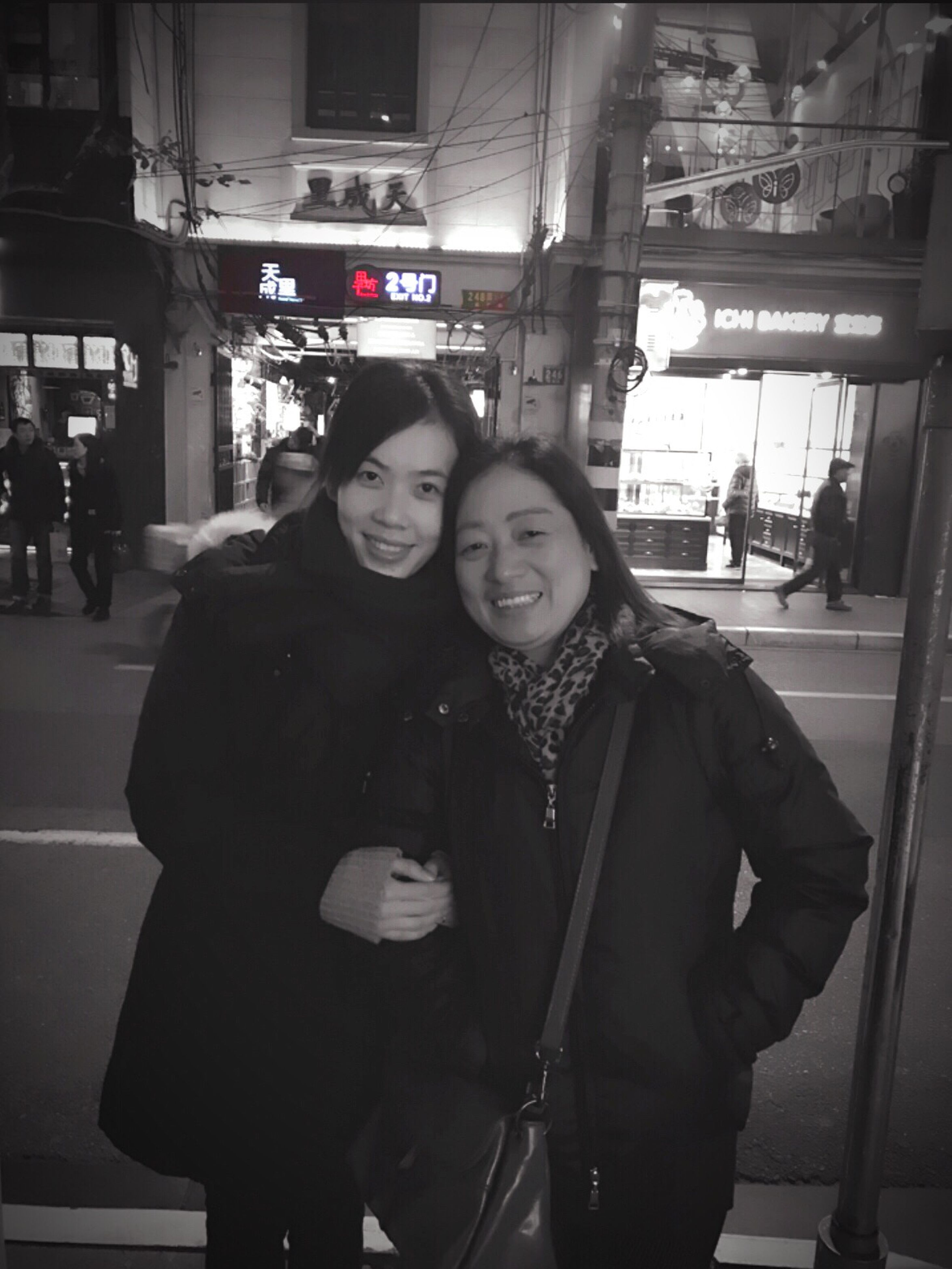 two people, smiling, women, portrait, young women, heterosexual couple, adults only, looking at camera, friendship, happiness, couple - relationship, young adult, city, togetherness, standing, people, adult, passenger, real people, night, men, bonding, public transportation, commuter, outdoors, railroad station platform, warm clothing, well-dressed