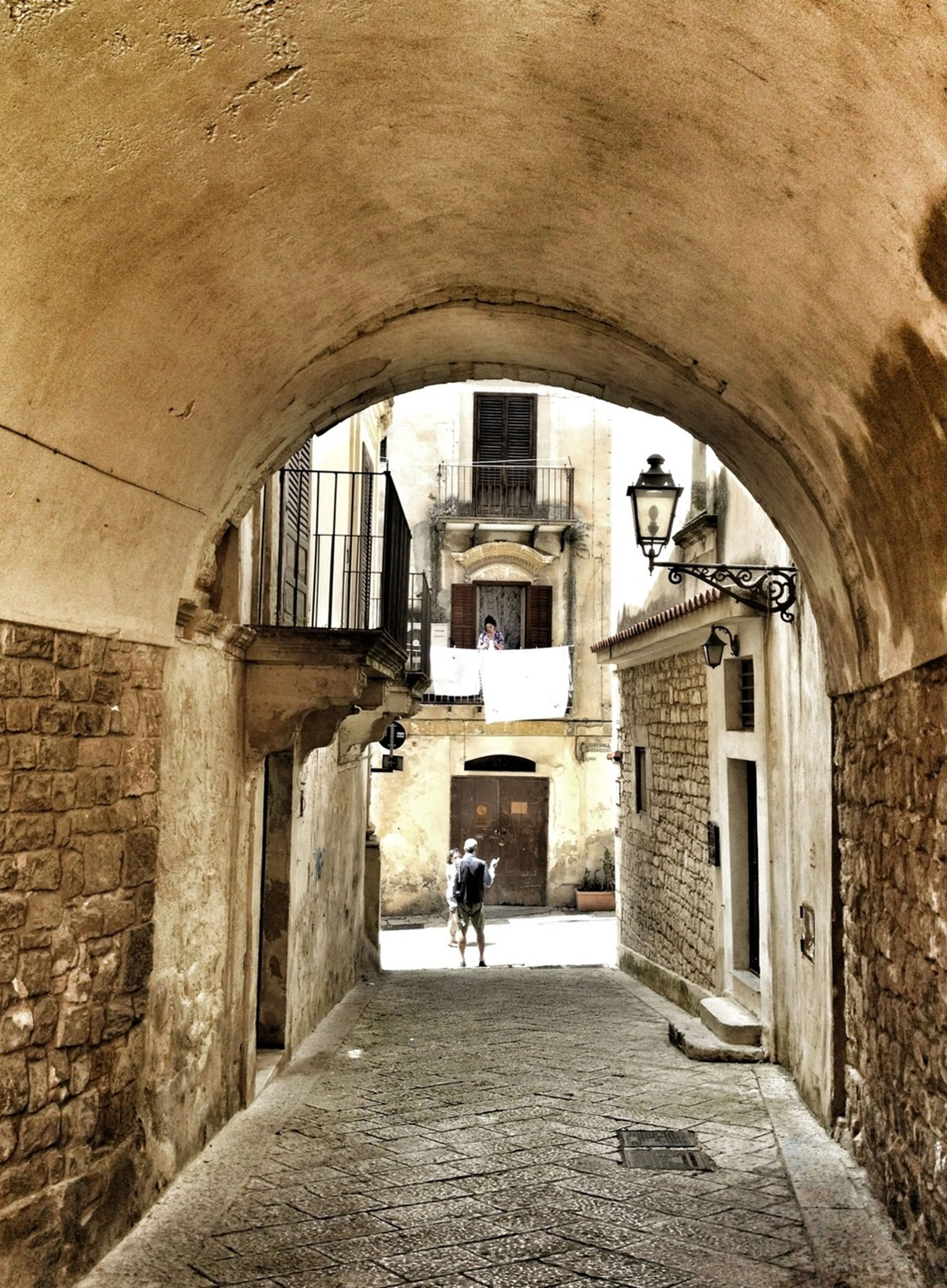 architecture, built structure, building exterior, arch, men, walking, building, the way forward, lifestyles, archway, tunnel, old, full length, cobblestone, residential building, indoors, street, abandoned