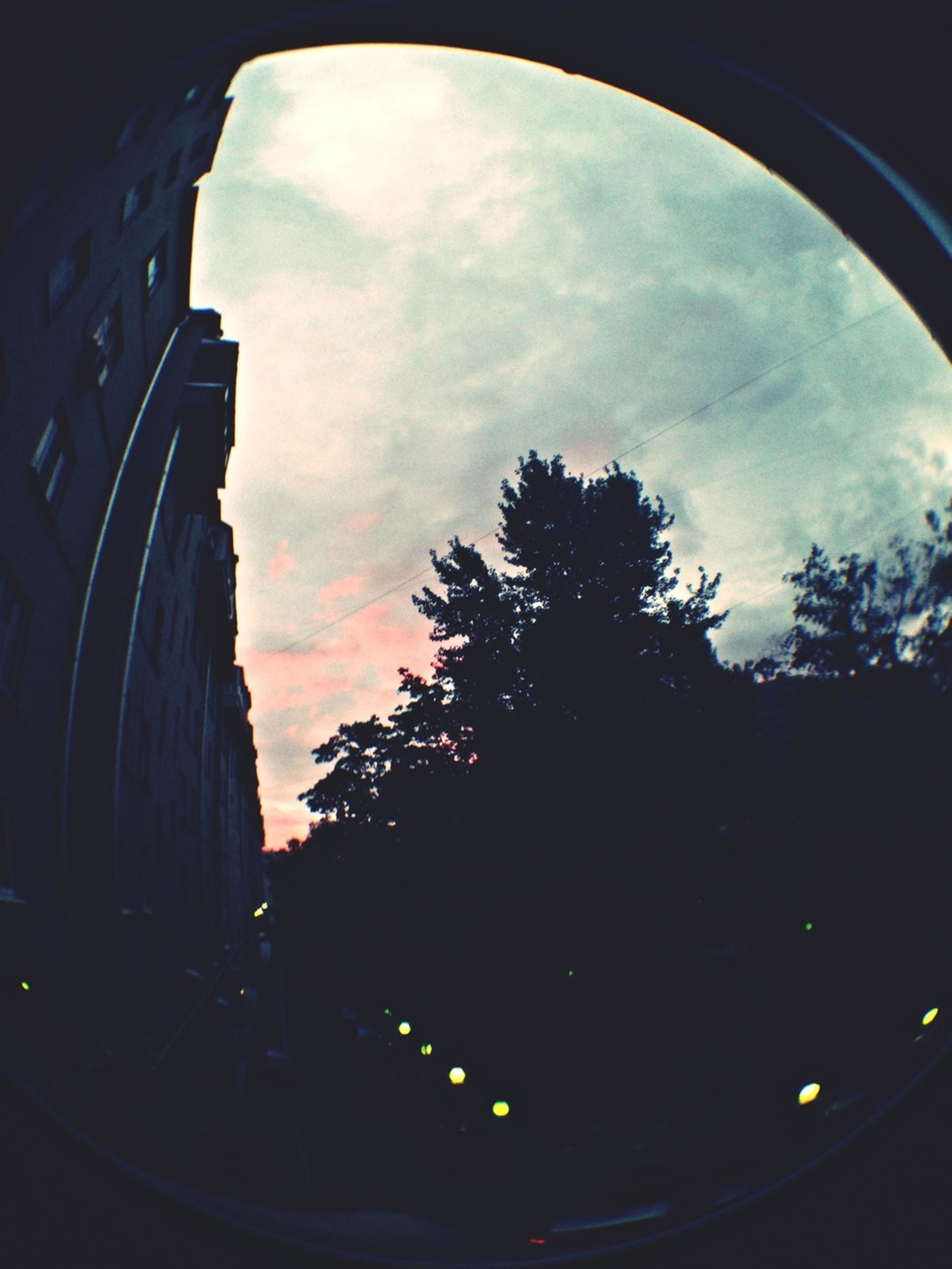 sky, cloud - sky, silhouette, built structure, architecture, tree, cloudy, low angle view, cloud, building exterior, arch, dusk, sunset, transportation, no people, fish-eye lens, window, circle, outdoors, nature