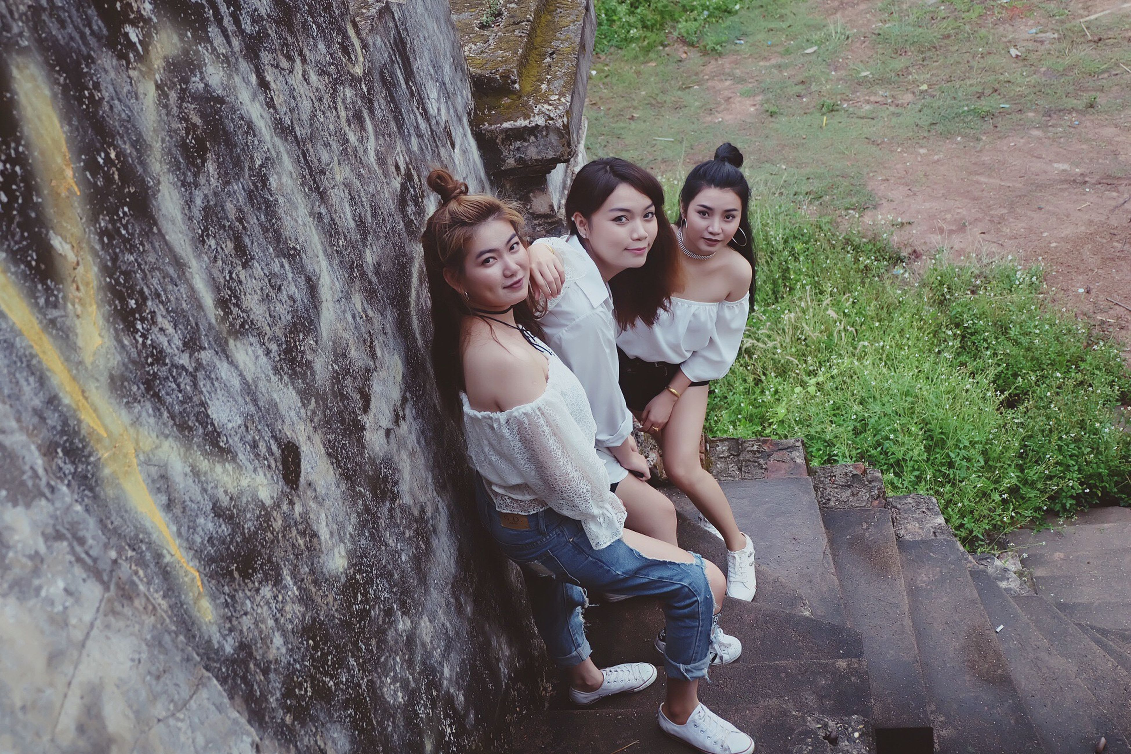 real people, full length, leisure activity, togetherness, casual clothing, outdoors, lifestyles, day, looking at camera, young women, high angle view, smiling, young adult, rock - object, happiness, family, girls, elementary age, portrait, childhood, love, bonding, tree, boys, two people, sitting, nature, retaining wall, architecture