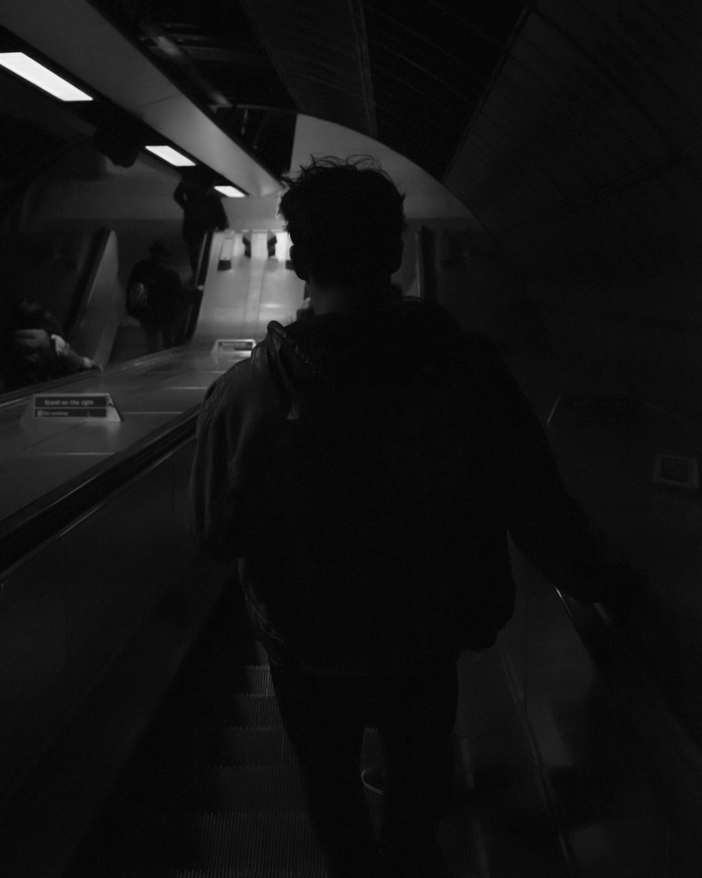 real people, rear view, transportation, standing, one person, travel, public transportation, lifestyles, illuminated, journey, men, full length, indoors, night, young adult, adult, people