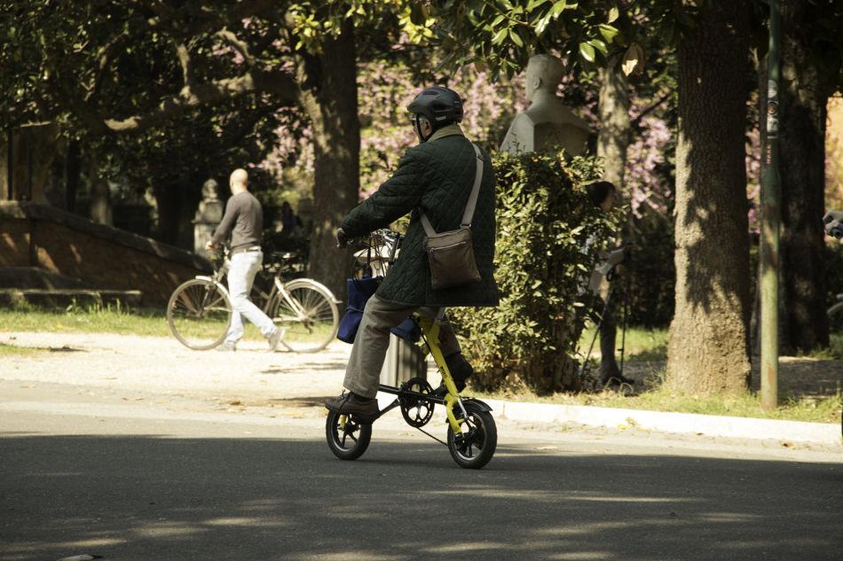 Man on Tiny Bike Bicycle Biker Helmet Leisure Activity Mode Of Transport Portable Riding Road Small Sunlight Tin Transportation