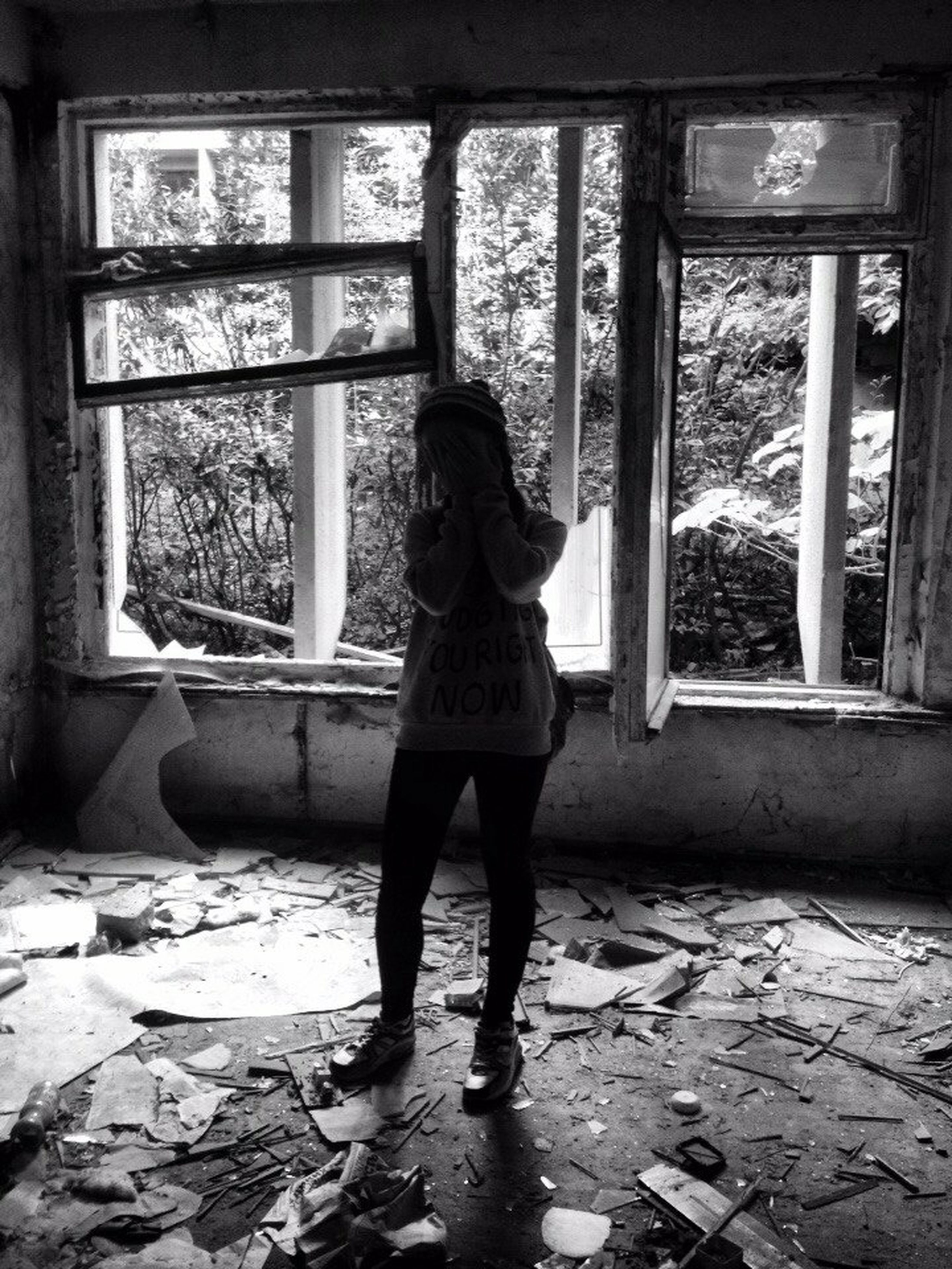 window, indoors, abandoned, full length, standing, built structure, architecture, lifestyles, house, day, damaged, obsolete, casual clothing, old, glass - material, leisure activity, door, weathered