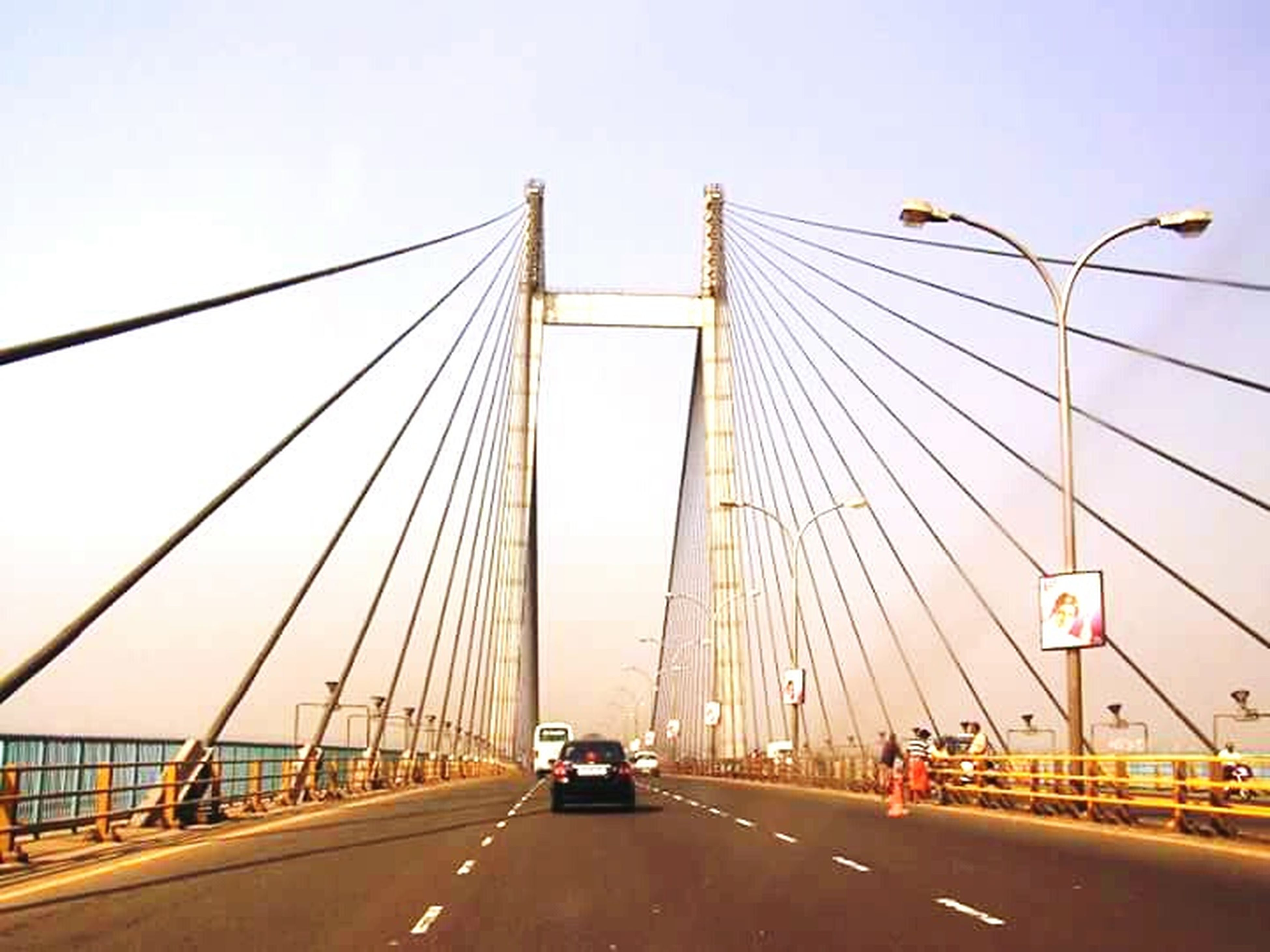 transportation, connection, bridge - man made structure, suspension bridge, road, engineering, car, the way forward, built structure, land vehicle, architecture, bridge, mode of transport, on the move, cable-stayed bridge, travel, road marking, travel destinations, clear sky, street light