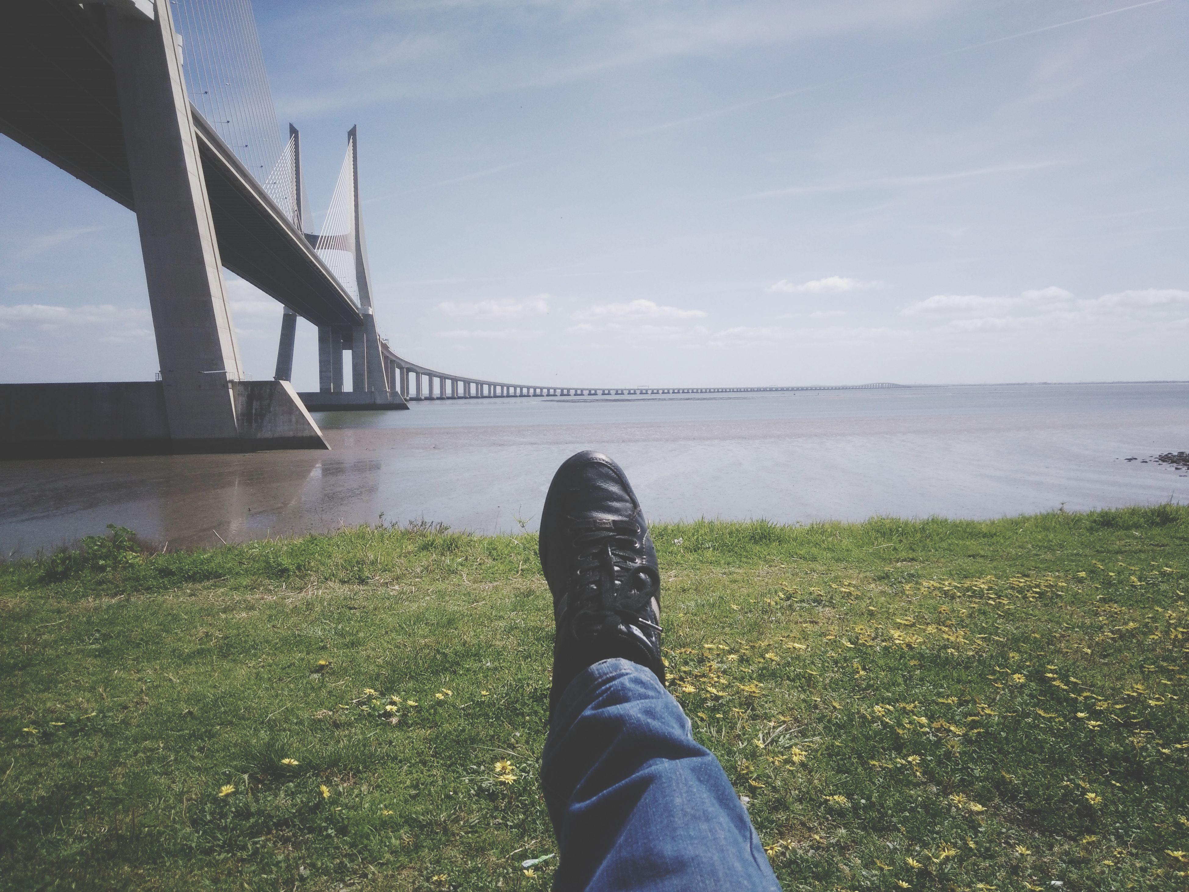 bridge - man made structure, human leg, low section, water, grass, connection, river, personal perspective, cloud - sky, day, sky, shoe, outdoors, one person, real people, human body part, nature, architecture