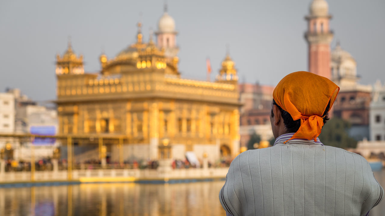 One man in front of the Golden Temple in Amritsar, India Amritsar Architecture Blurred Blurred Background Copy Space Golden Golden Temple Gurdwara Harmandir Sahib Holy India Meditation One Person Punjab Rear View Sikh Sikhism Temple Travel Destinations Worship