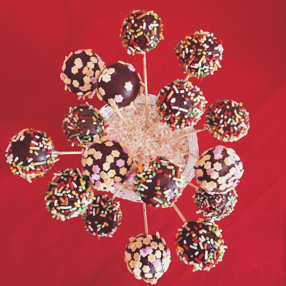 Colorful chocolate cakepops with sprinkles on red background top view Above Cake Cakepop Cakepops Candy Chocolate Colorful Delicious Dessert Directly Above Food Gourmet Indoors  Many Pastry Popcake Red Sprinkles Stick Sweet Table Top View Various