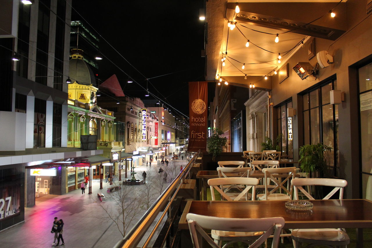 illuminated, night, restaurant, architecture, built structure, cafe, chair, city, building exterior, indoors, food, no people