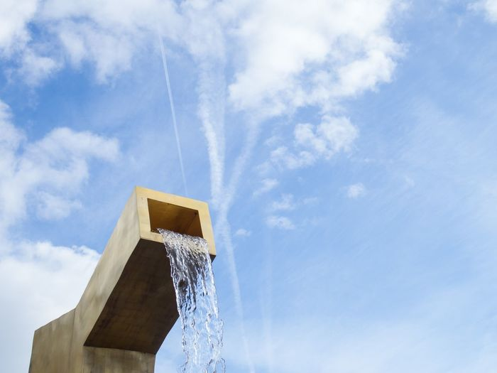 Water sculpture on the main square Blue Sky And Clouds Cloud - Sky Copy Space Fountain Gold Colored Golden Low Angle View Sculpture Sky Waterfall