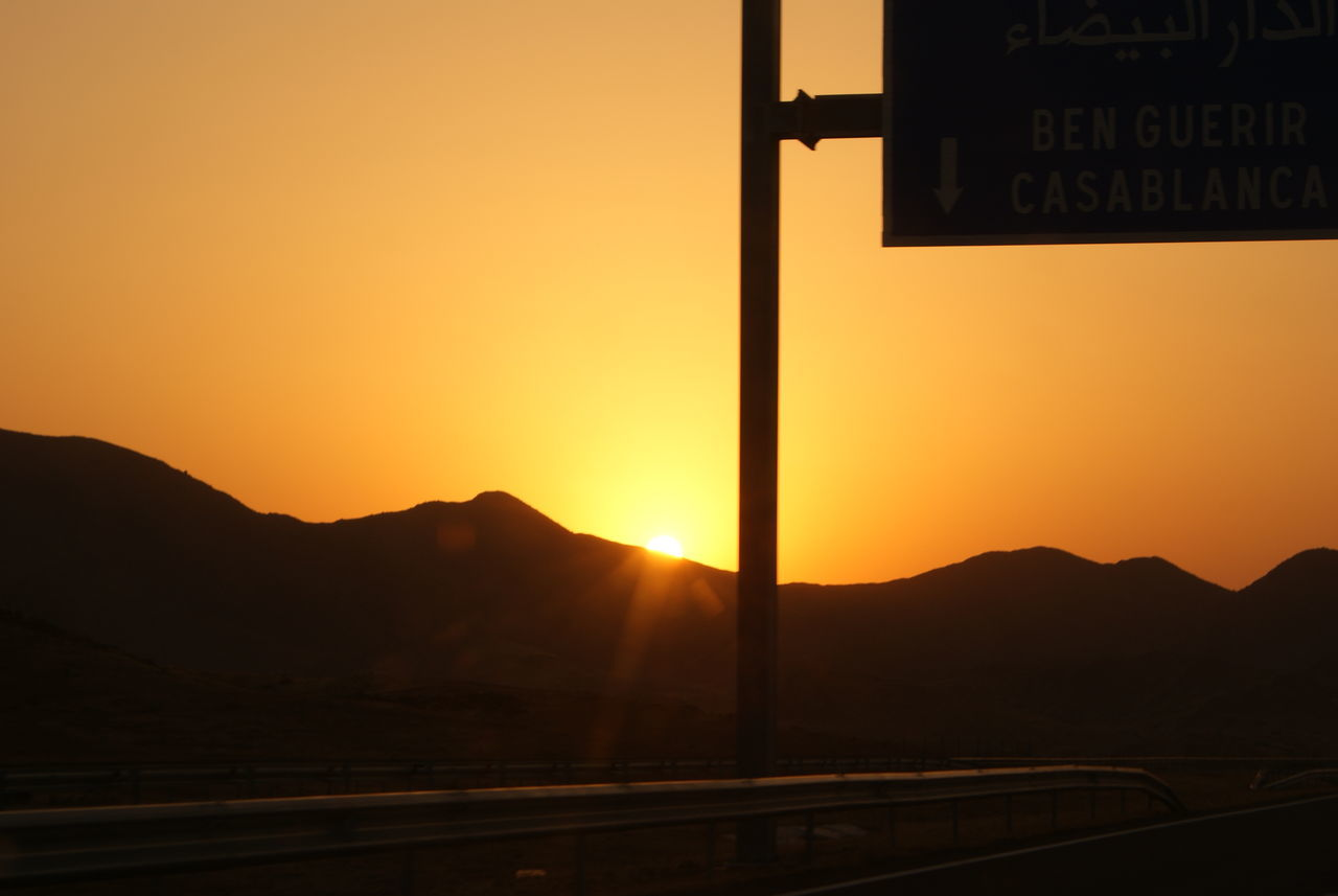 sunset, mountain, orange color, silhouette, outdoors, no people, transportation, scenics, beauty in nature, mountain range, nature, road, sky, road sign, day