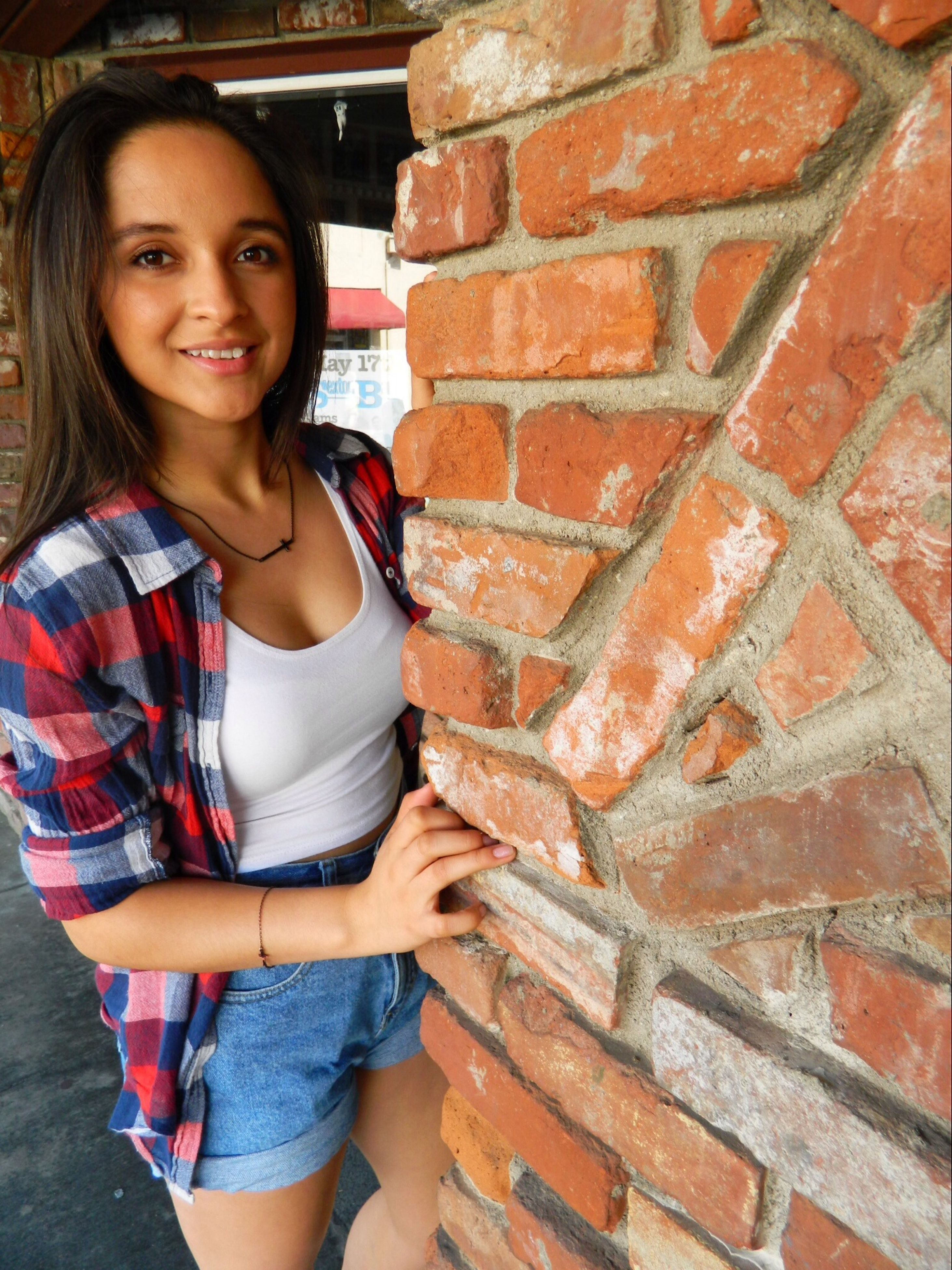 person, young adult, looking at camera, portrait, lifestyles, young women, casual clothing, smiling, front view, leisure activity, standing, happiness, three quarter length, long hair, wall - building feature, brick wall