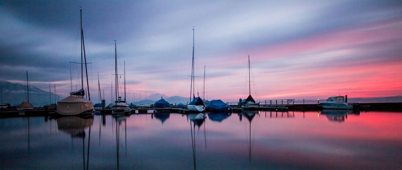 View Of Boats At Harbor During Sunset