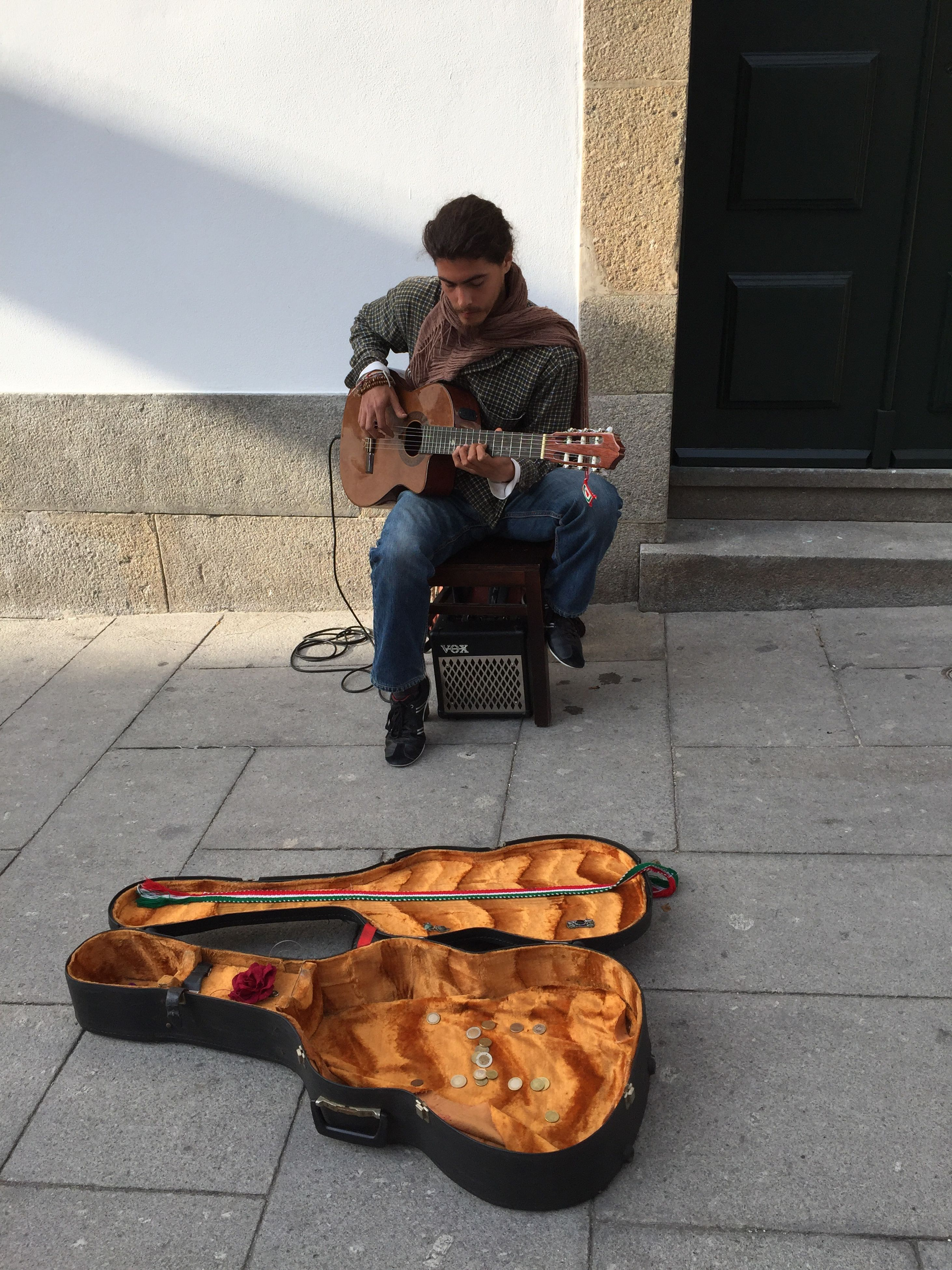 sitting, full length, one person, music, playing, musical instrument, guitar, casual clothing, leisure activity, musician, real people, shoe, outdoors, arts culture and entertainment, holding, men, day, lifestyles, young adult, people