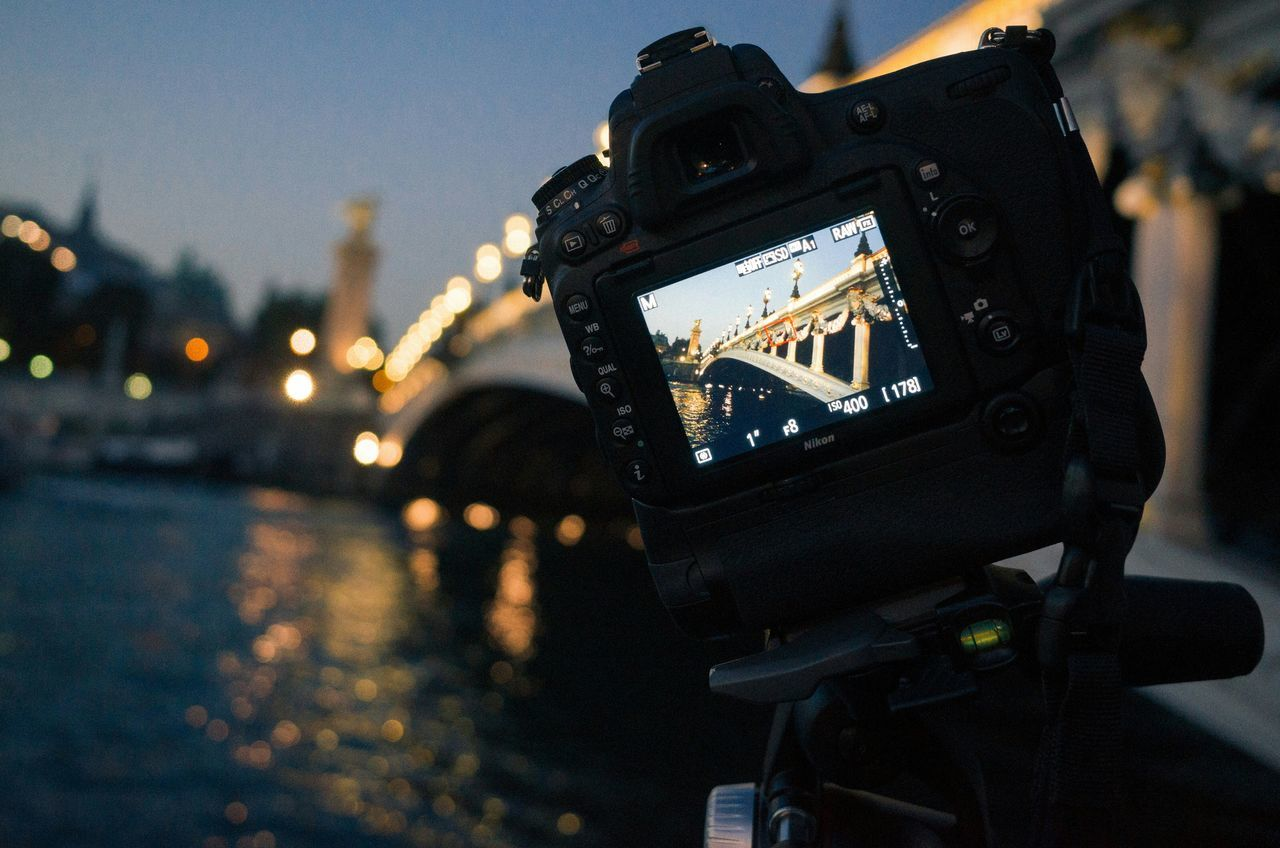 camera - photographic equipment, photography themes, technology, focus on foreground, photographing, digital camera, illuminated, no people, close-up, outdoors, camera, digital single-lens reflex camera, city, day