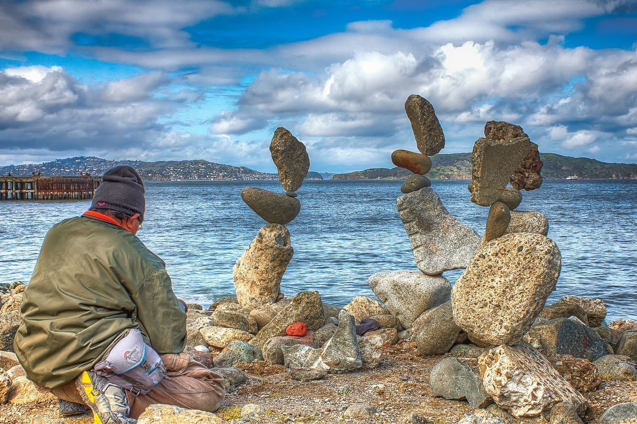 sea, rock - object, cloud - sky, sky, one person, sitting, real people, water, nature, beauty in nature, lifestyles, men, horizon over water, scenics, outdoors, day, beach, warm clothing, adult, people, adults only