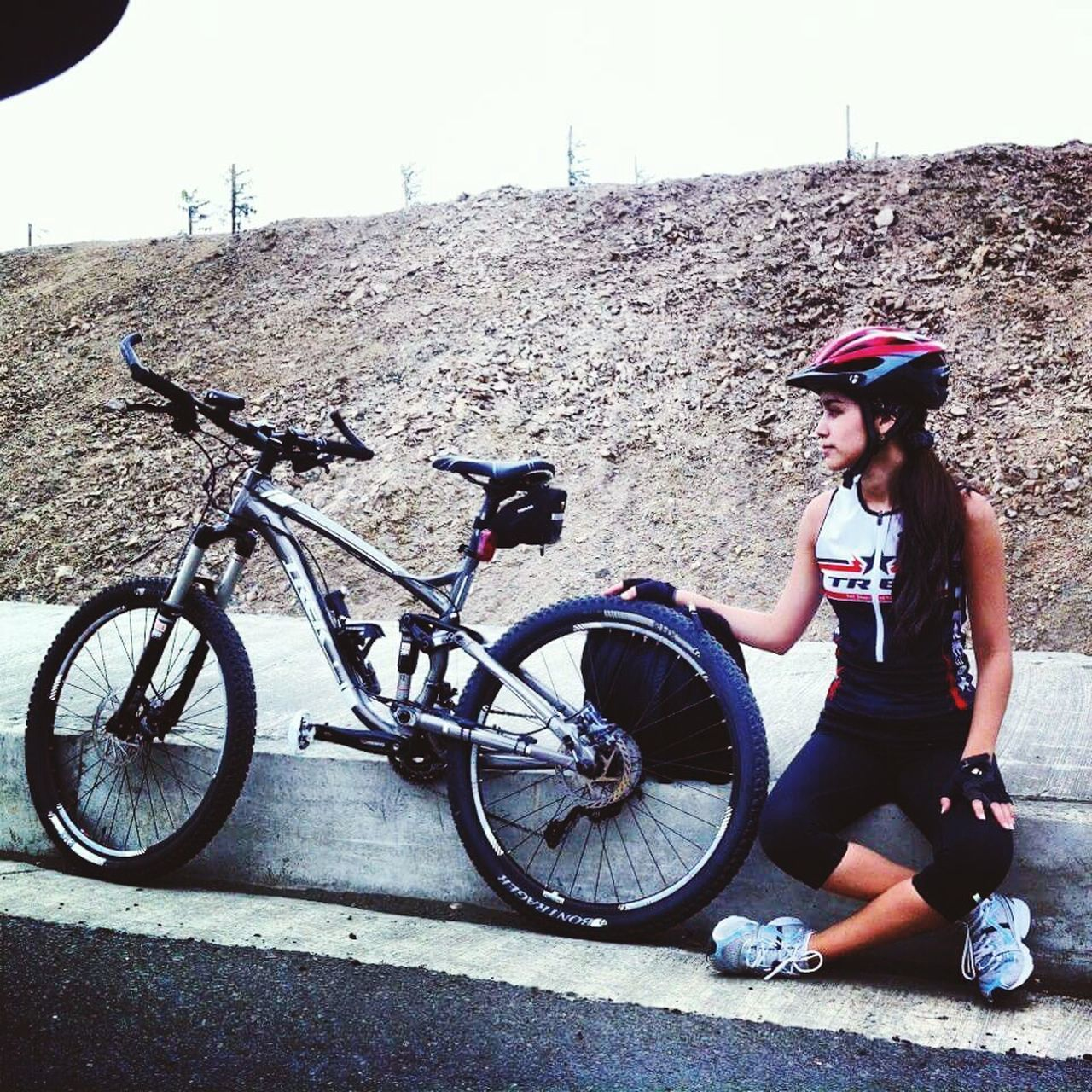 bicycle, real people, transportation, one person, mode of transport, cycling, land vehicle, full length, lifestyles, outdoors, day, leisure activity, cycling helmet, stationary, riding, adventure, young women, headwear, sports helmet, mountain bike, nature, young adult, sky, people