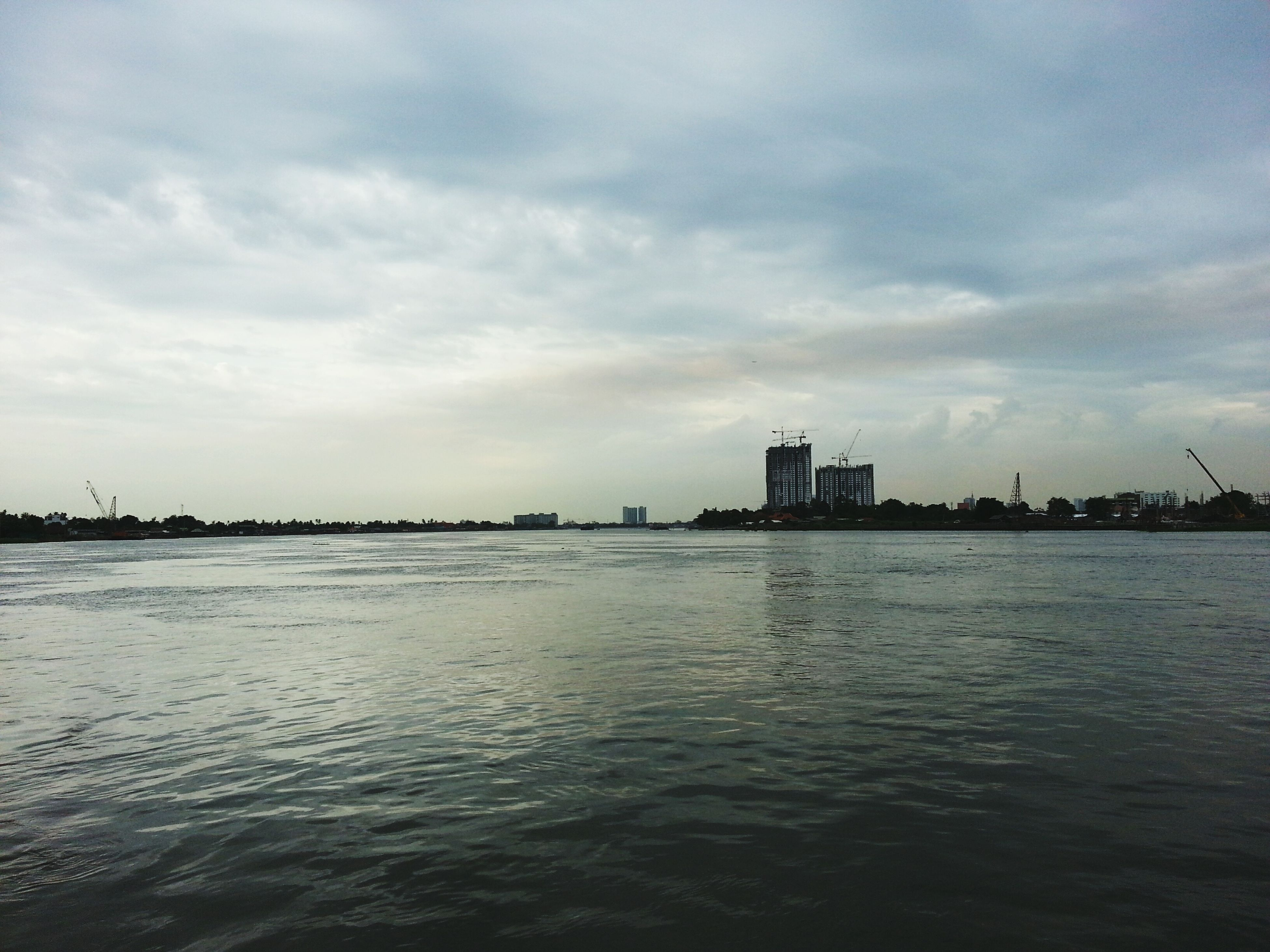water, waterfront, building exterior, sky, architecture, built structure, sea, cloud - sky, city, cloudy, rippled, cloud, scenics, nature, tranquil scene, tranquility, river, beauty in nature, dusk, cityscape