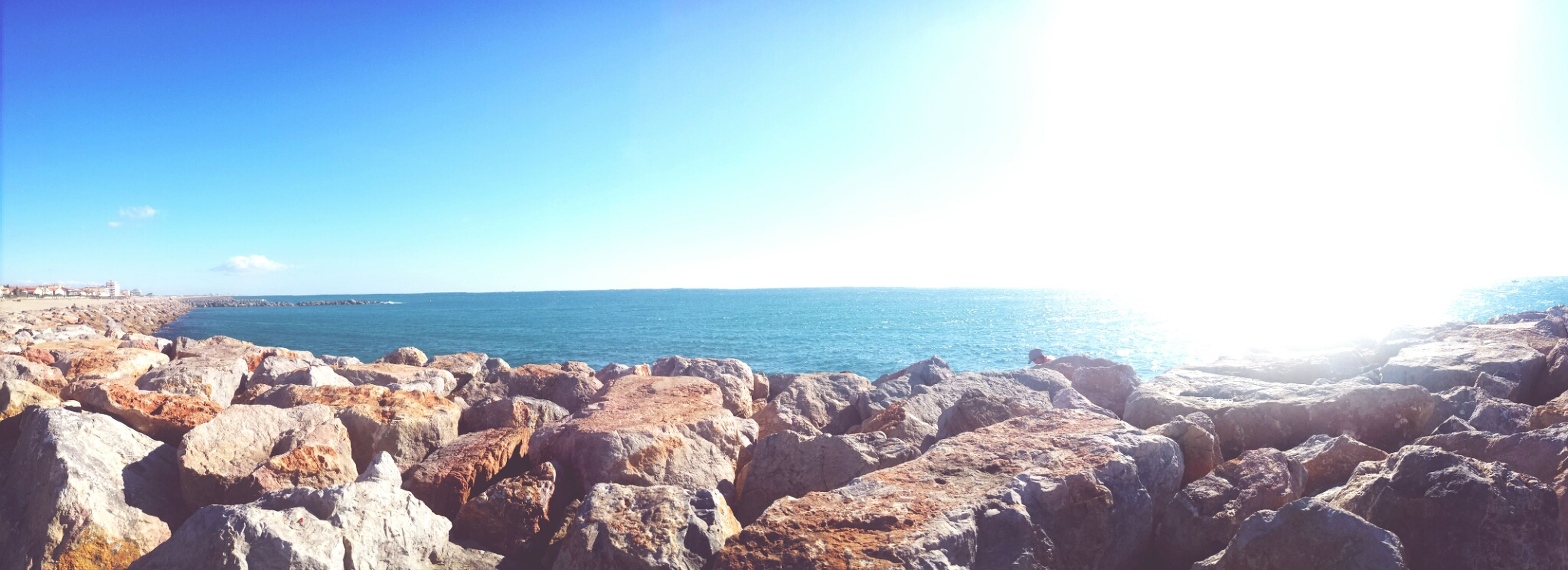 sea, horizon over water, scenics, water, tranquil scene, rock - object, beauty in nature, tranquility, clear sky, nature, rock formation, blue, sky, idyllic, sunlight, rock, copy space, sun, remote, non-urban scene