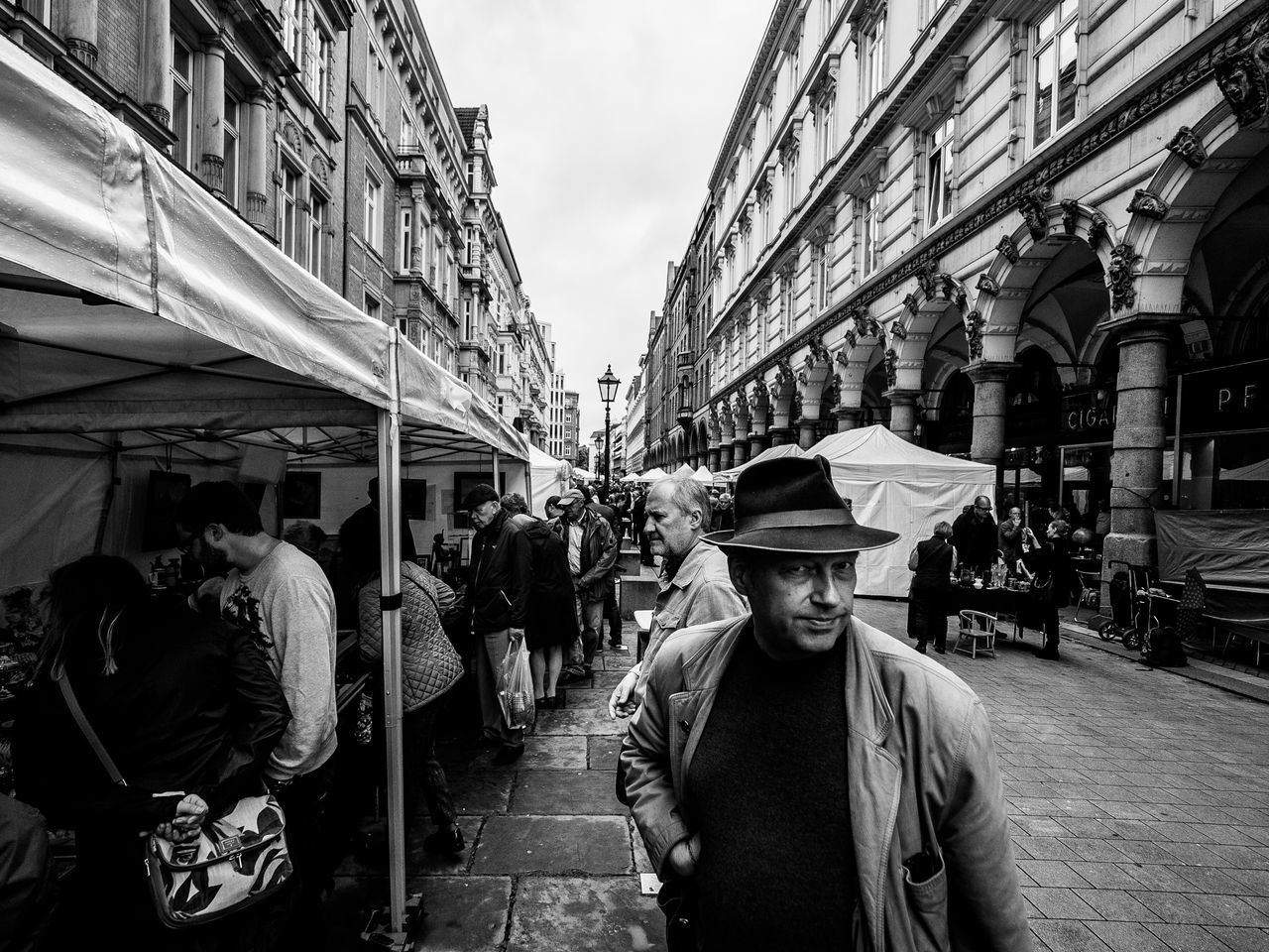 Stall // Hamburg Building Exterior Real People Architecture Built Structure Men City Street Casual Clothing Standing Outdoors Store Day Lifestyles Large Group Of People Sky Adult Only Men Adults Only People Streetphotography Monochrome Blackandwhite Eye Contact Wide Angle The Street Photographer - 2017 EyeEm Awards