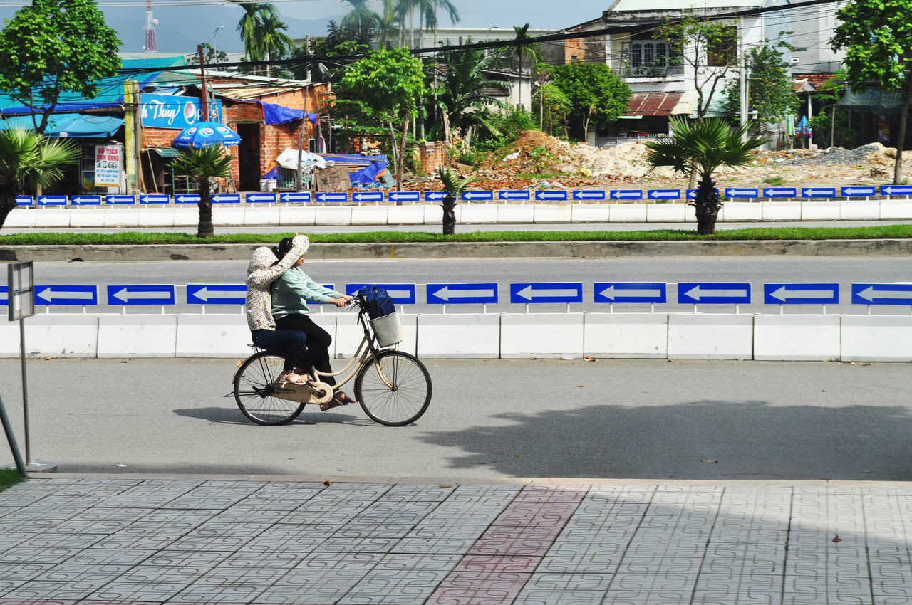 Girls share pedal power and sun protection while cycling along street in Da Nang, Vietnam. Architecture Arrows Bicycle City Concrete Barrier Cycling Da Nang Day Editorial  Friends Girls Lifestyle Outdoors Palm Trees Pedalling Sharing  Street Students Sun Protection Tree Vietnam