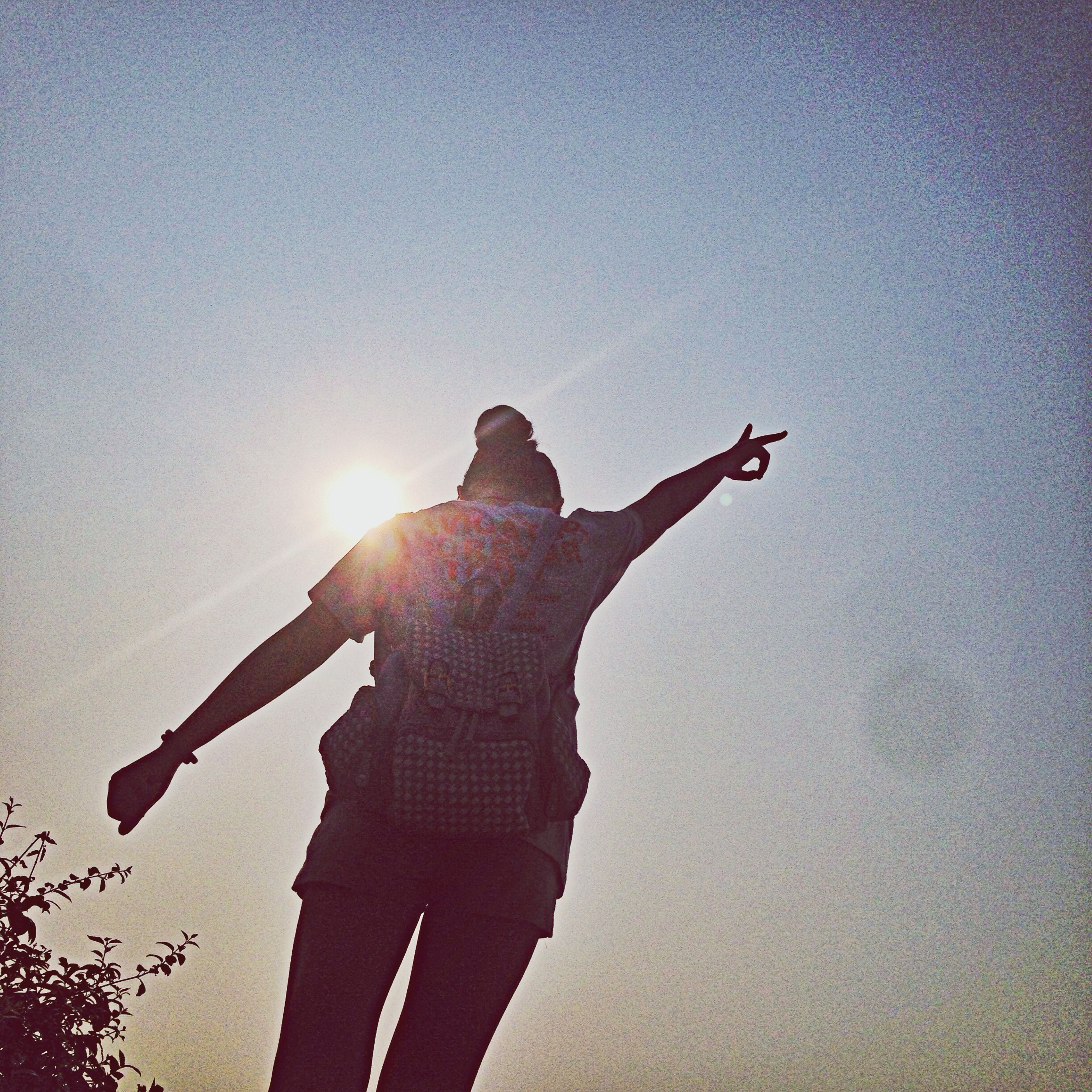 sun, silhouette, leisure activity, lifestyles, sunlight, sunbeam, low angle view, lens flare, holding, men, sky, standing, sunset, back lit, outdoors, copy space, skill, unrecognizable person