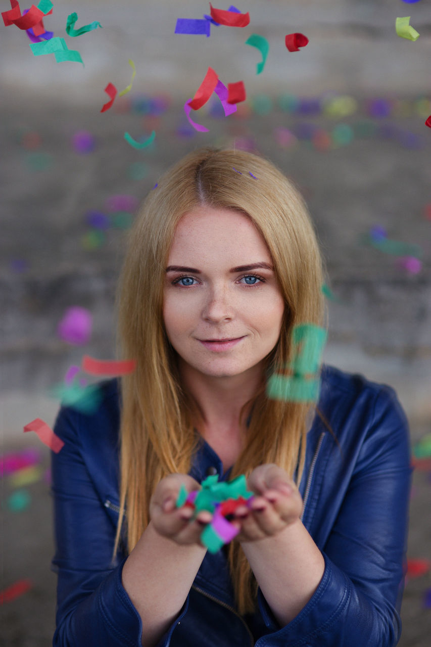 Portrait Of Smiling Young Woman Holding Confetti