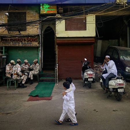 Two Indian Muslim children look at a group of cops deployed for security purposes on Eid al-Adha near Jama Masjid, Delhi, as they walk past them. Everydayeverywhere Dailylife Photojournalism Journalism Indiaphotoproject Reportagespotlight _soi Dfordelhi Sodelhi DelhiGram Delhi Newdelhi ASIA India